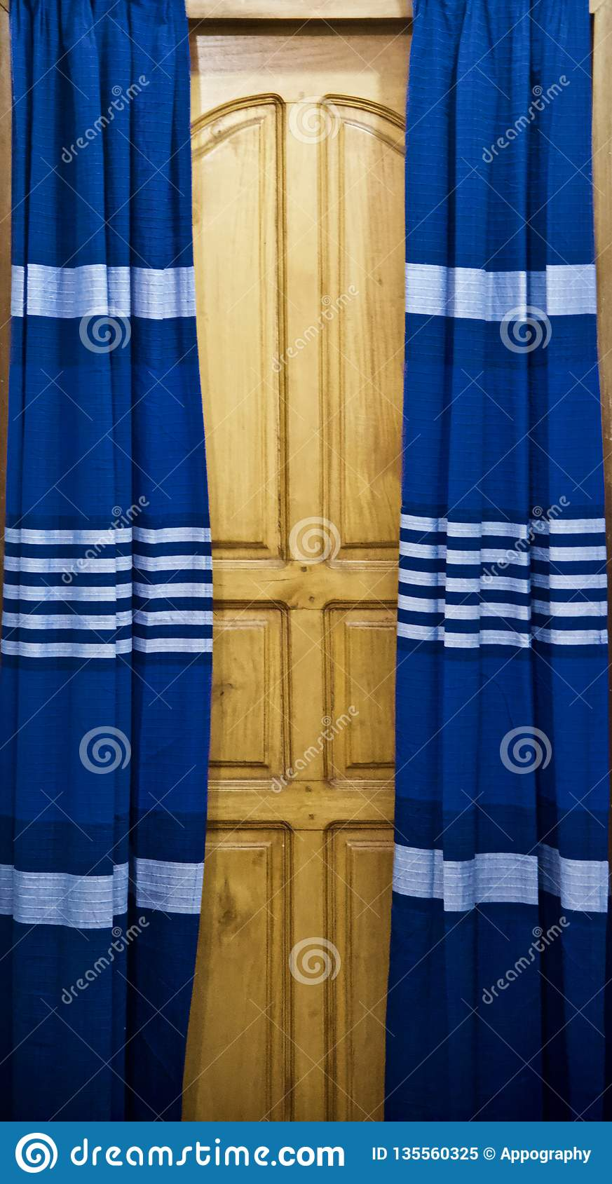 Blueish curtain clothes of a wooden door