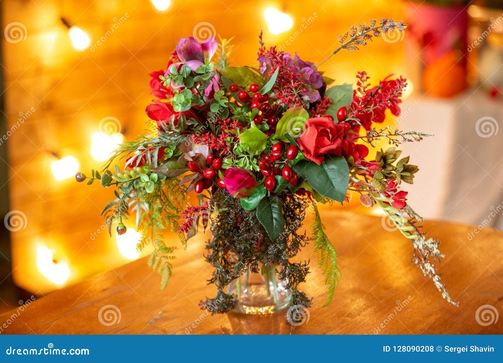 Blumenanordnung mit roten Beeren, roten Rosen und Grüns auf dem Tisch