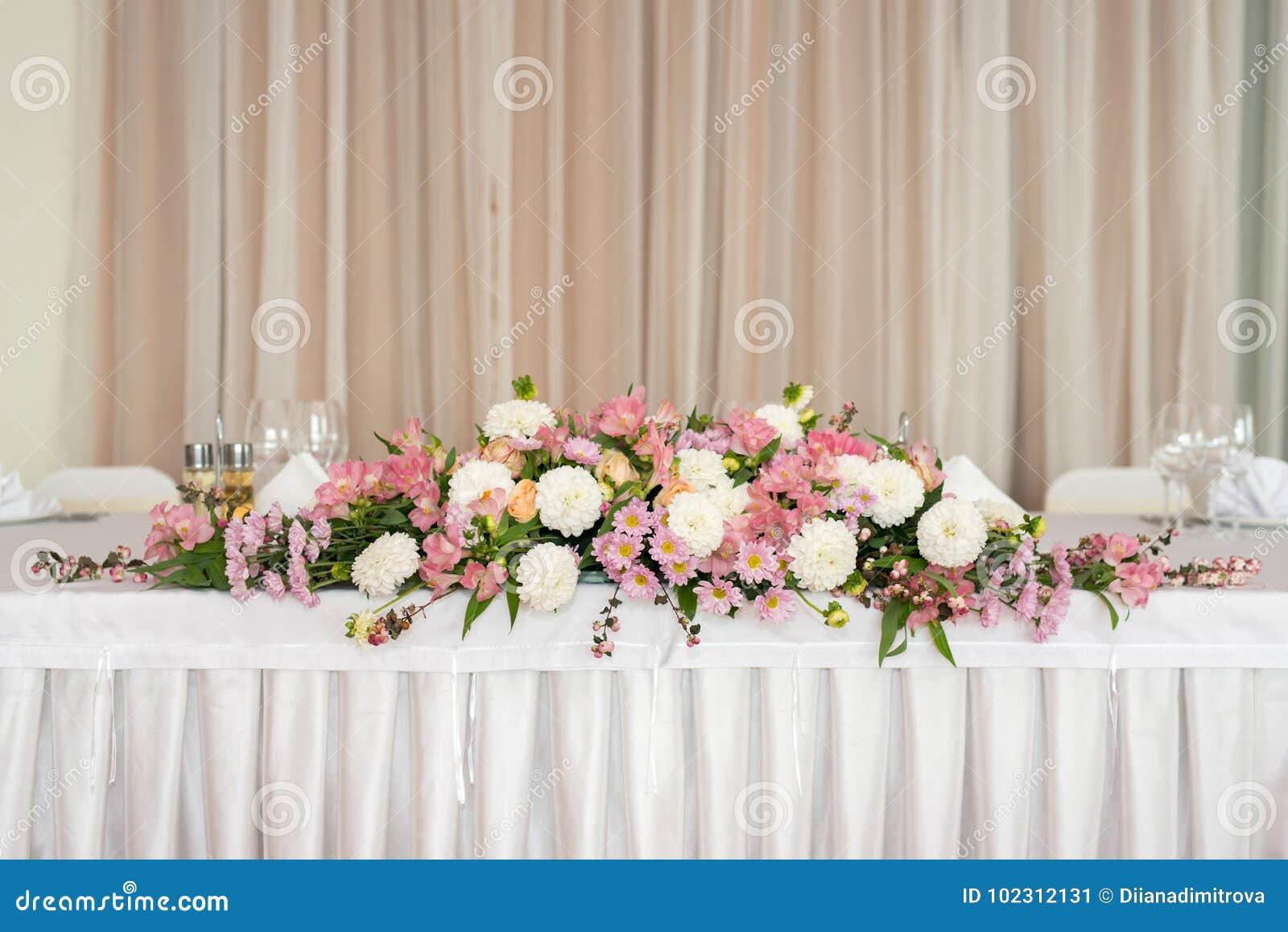 Blumendekoration der schönen Hochzeit auf einer Tabelle in einem Restaurant Weiße Tischdecken, heller Raum