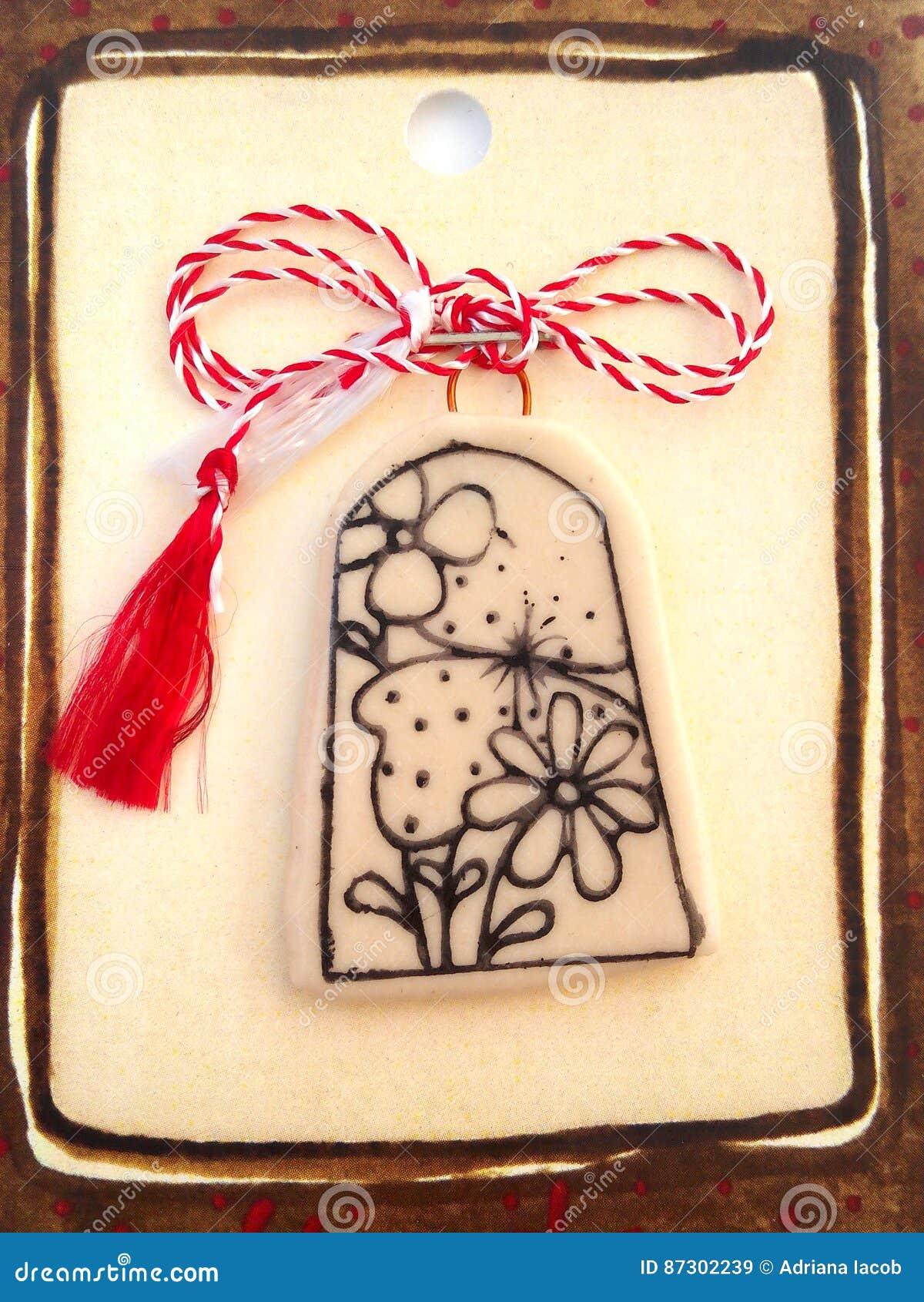 Blumenmedaillon mit roter und weißer Schnur