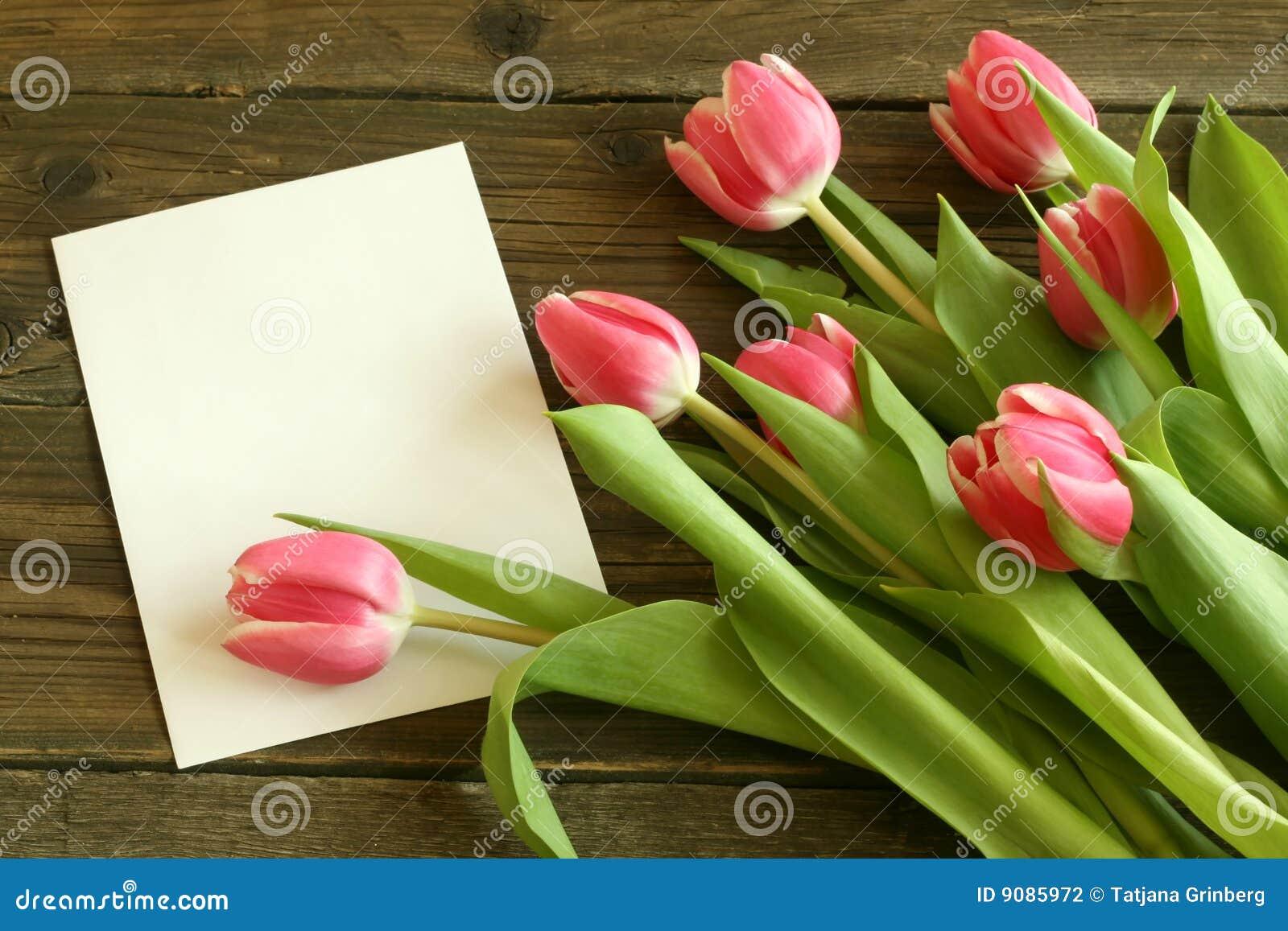 Blumenstrauß der Tulpen mit unbelegter Karte auf altem hölzernem