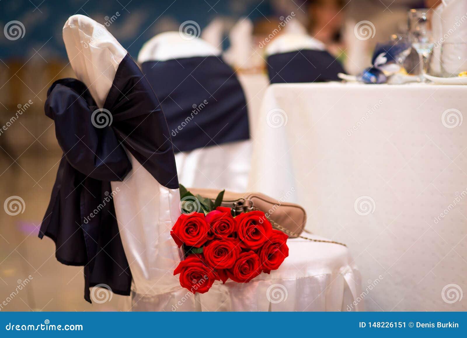 Blumenstrauß von roten Rosen auf einem Stuhl ein Geschenk an der Hochzeit Blumen als Geschenk Heiratsdekoration des Restaurants