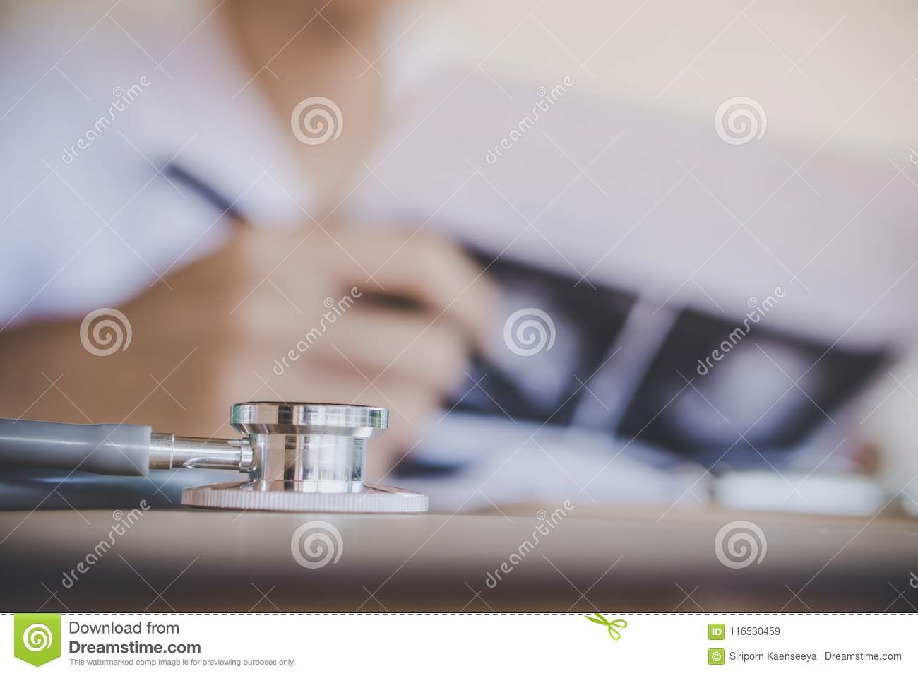 Stethoscope on desk with doctor working in office