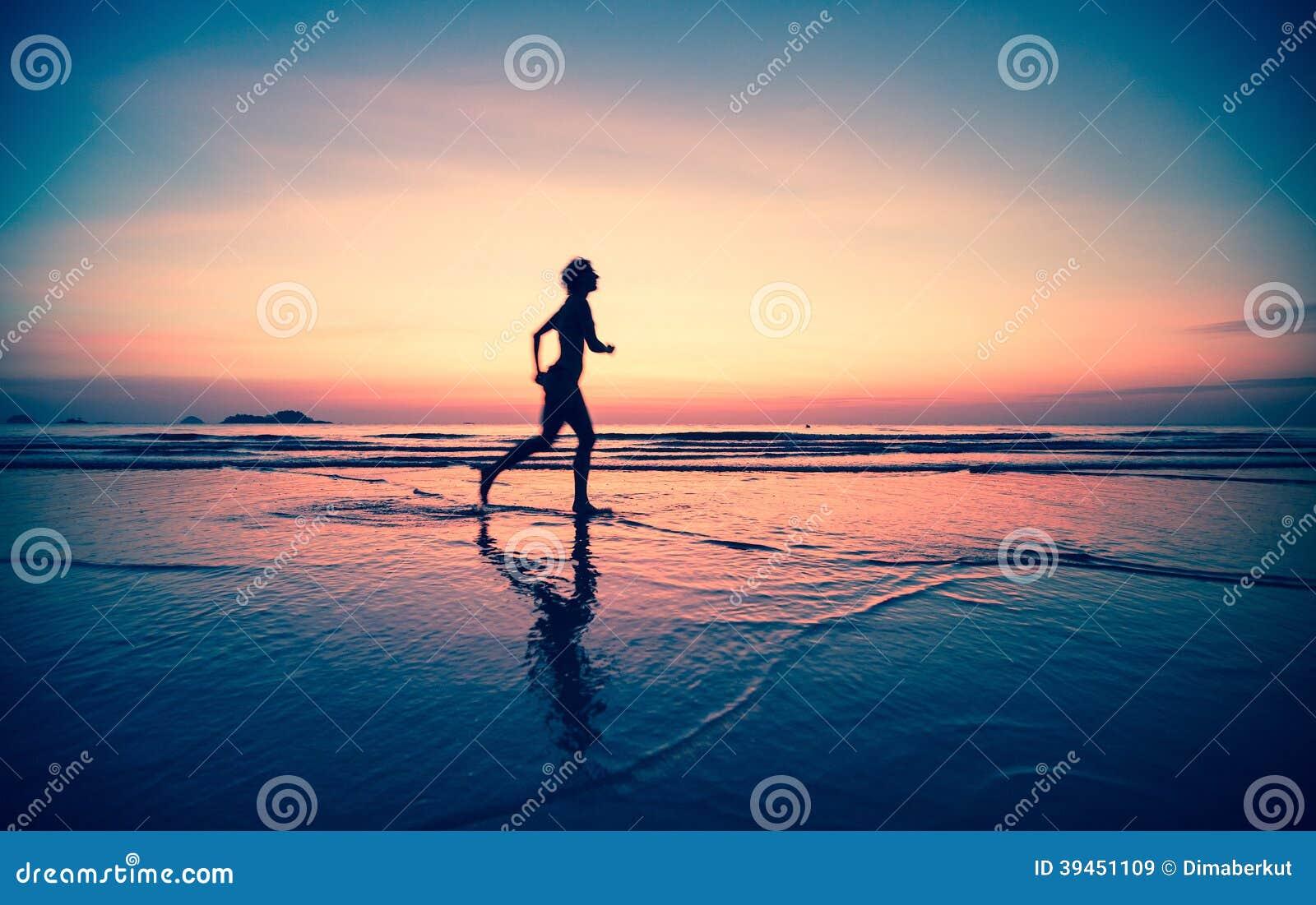 Blured kontur av en kvinnajogger på stranden på solnedgången