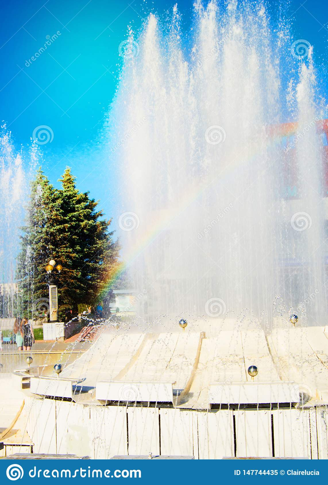 Blurred colorful rainbow on a background of splashing fountain on a Sunny summer day, vertical shot