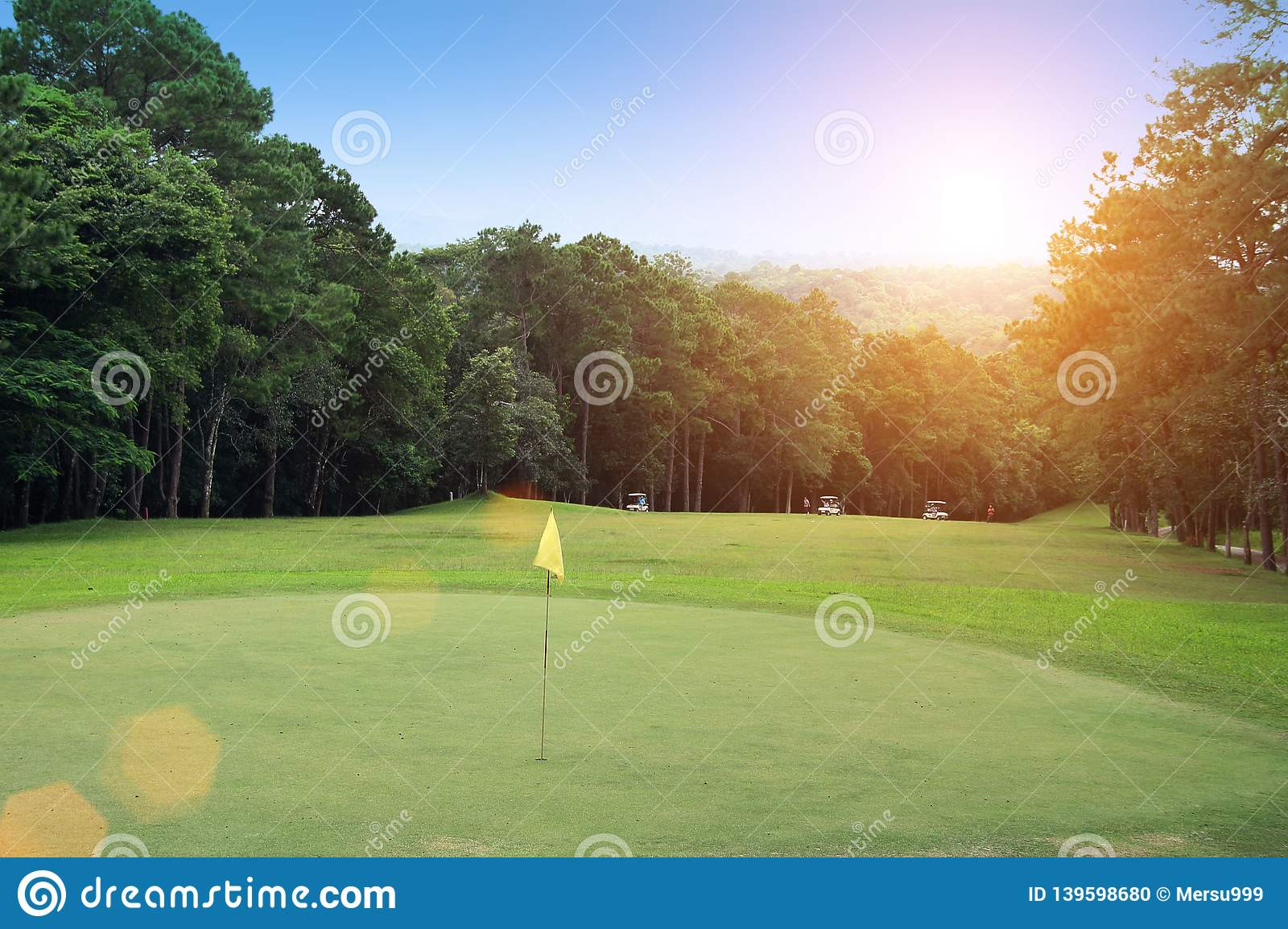 Blurred golf ball on tee in beautiful golf course with sunset.