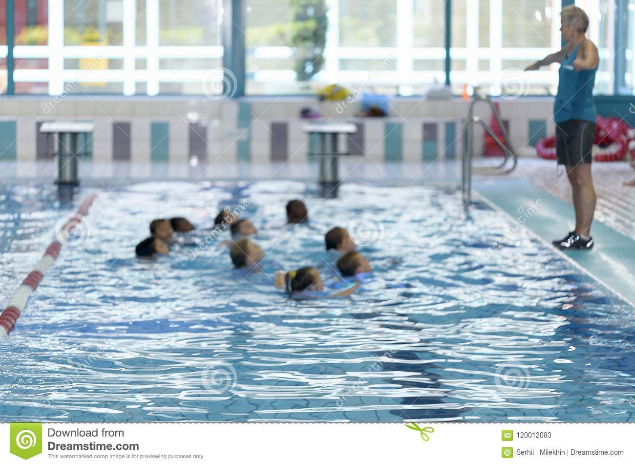 Blurred. Group of Children learn to swim in the pool