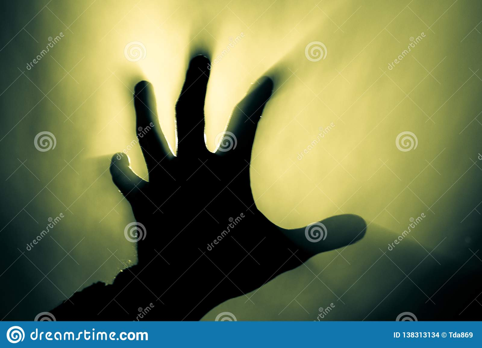 Blurred hand in smoke in a fire in the harsh light of the sun