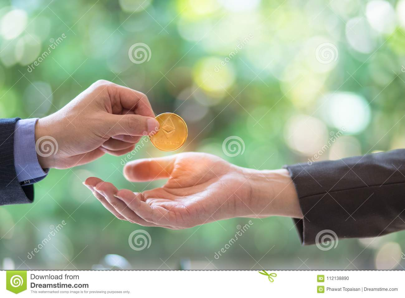 Blurred Hands of two businessmen are trading coin of ethereum. A symbolic coins of ethereum. electronic money exchange,