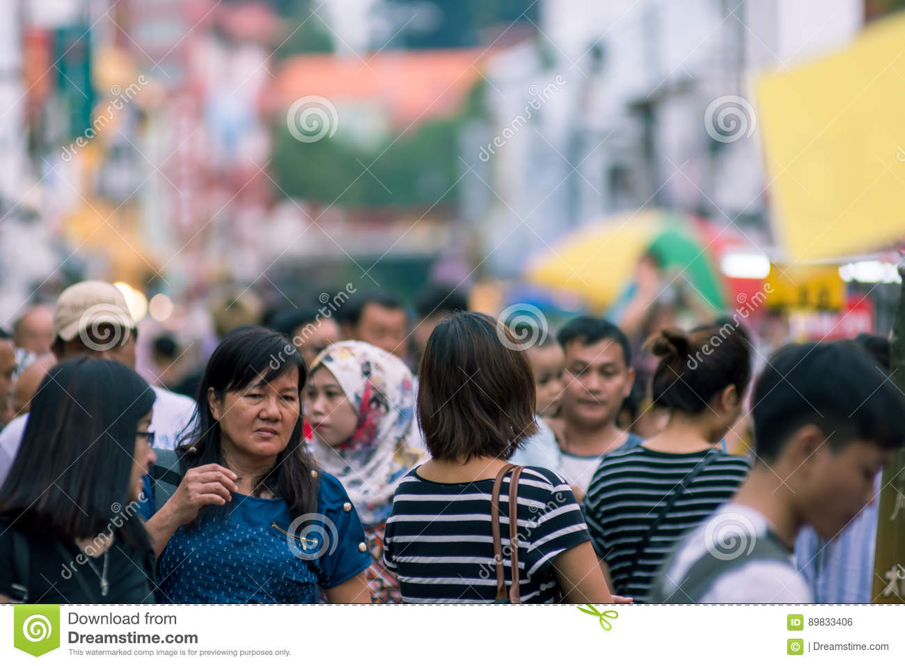 Blurred image of a crowd of people at a street market. Malacca,