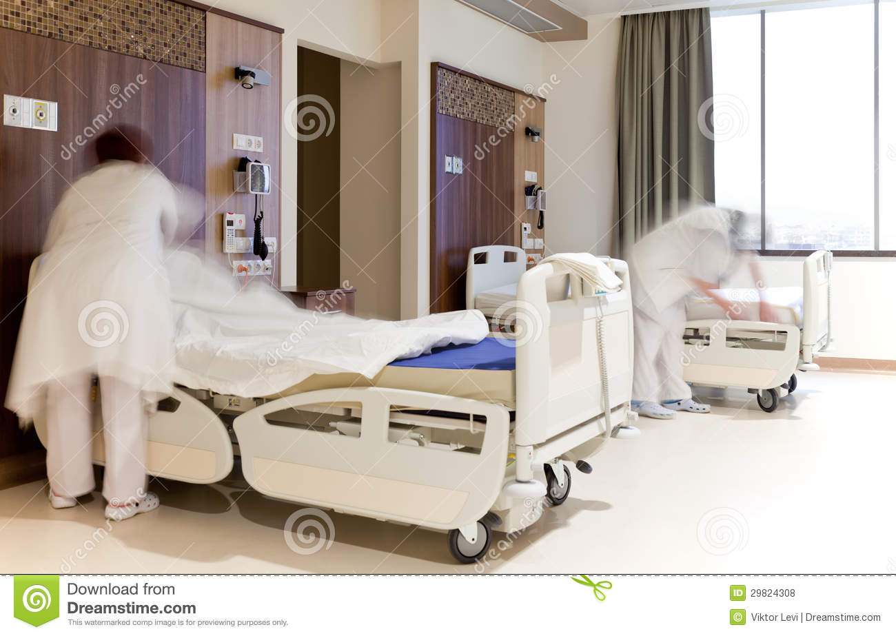 Blurred Images Of Staff Members Changing Hospital Bed Sheets In Modern  Equipped Room