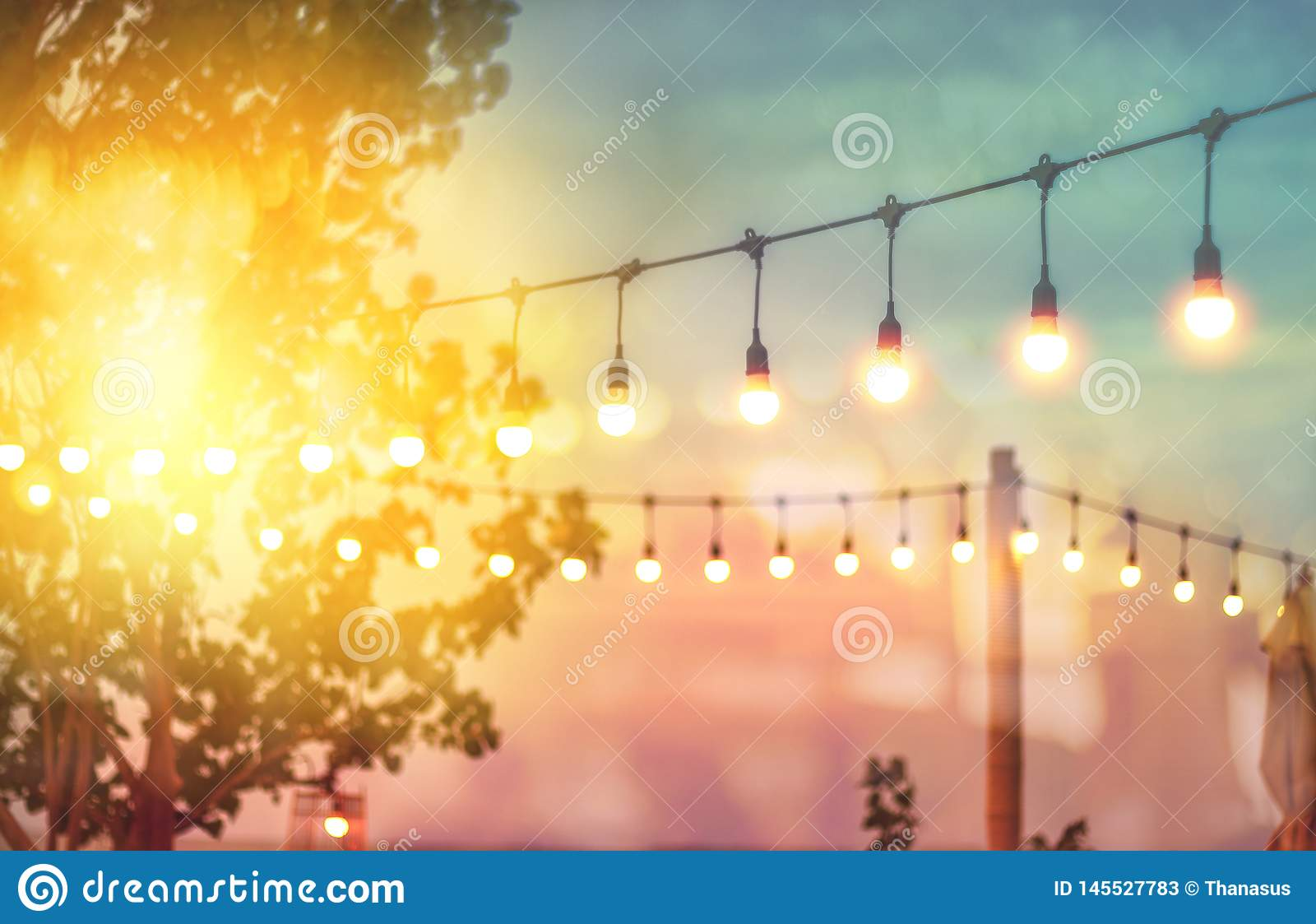 Blurred light on sunset with yellow string lights decor in beach restaurant