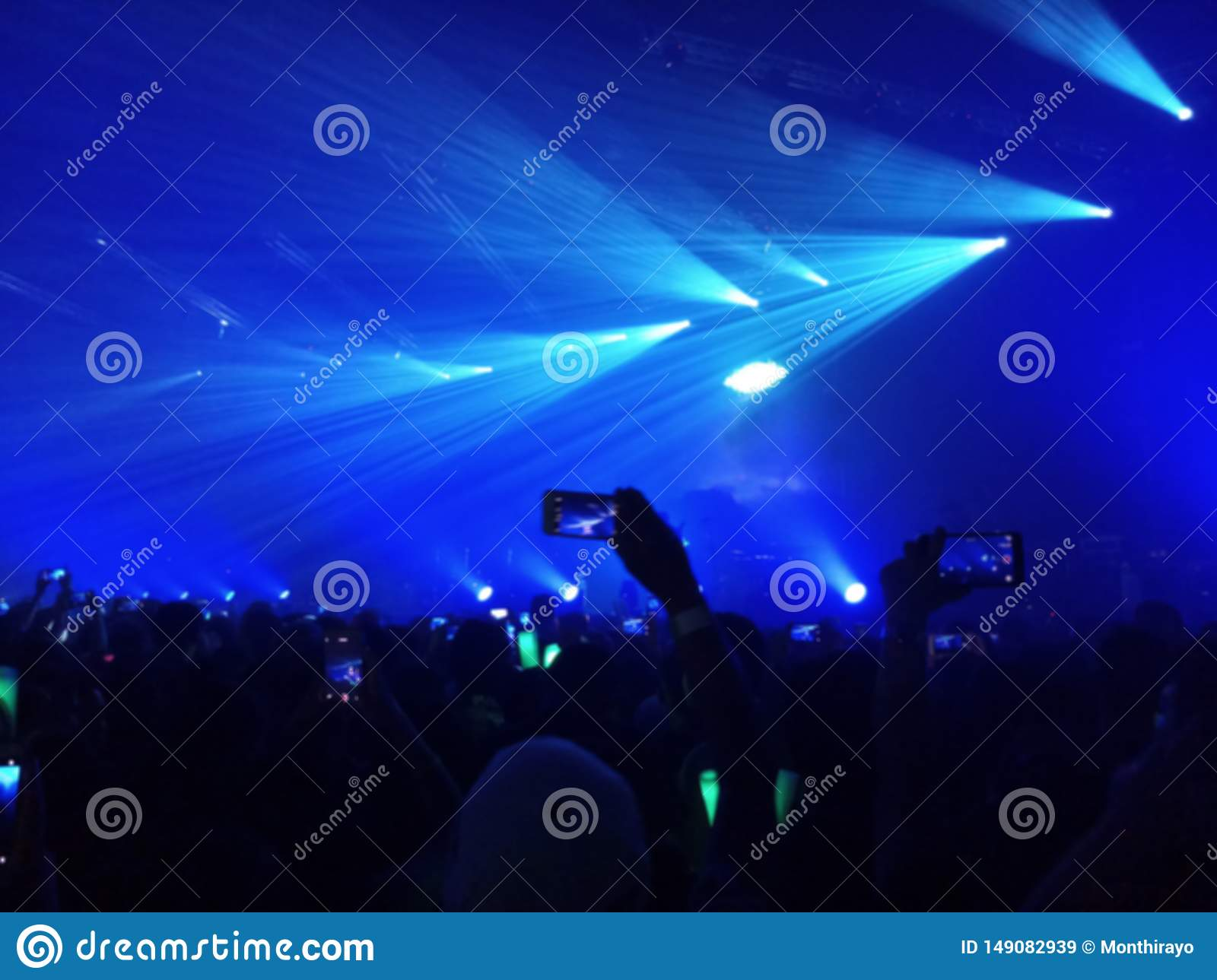 Blurred photo of people using a smart phone to take a photo of music festival and lights streaming down, rock concert