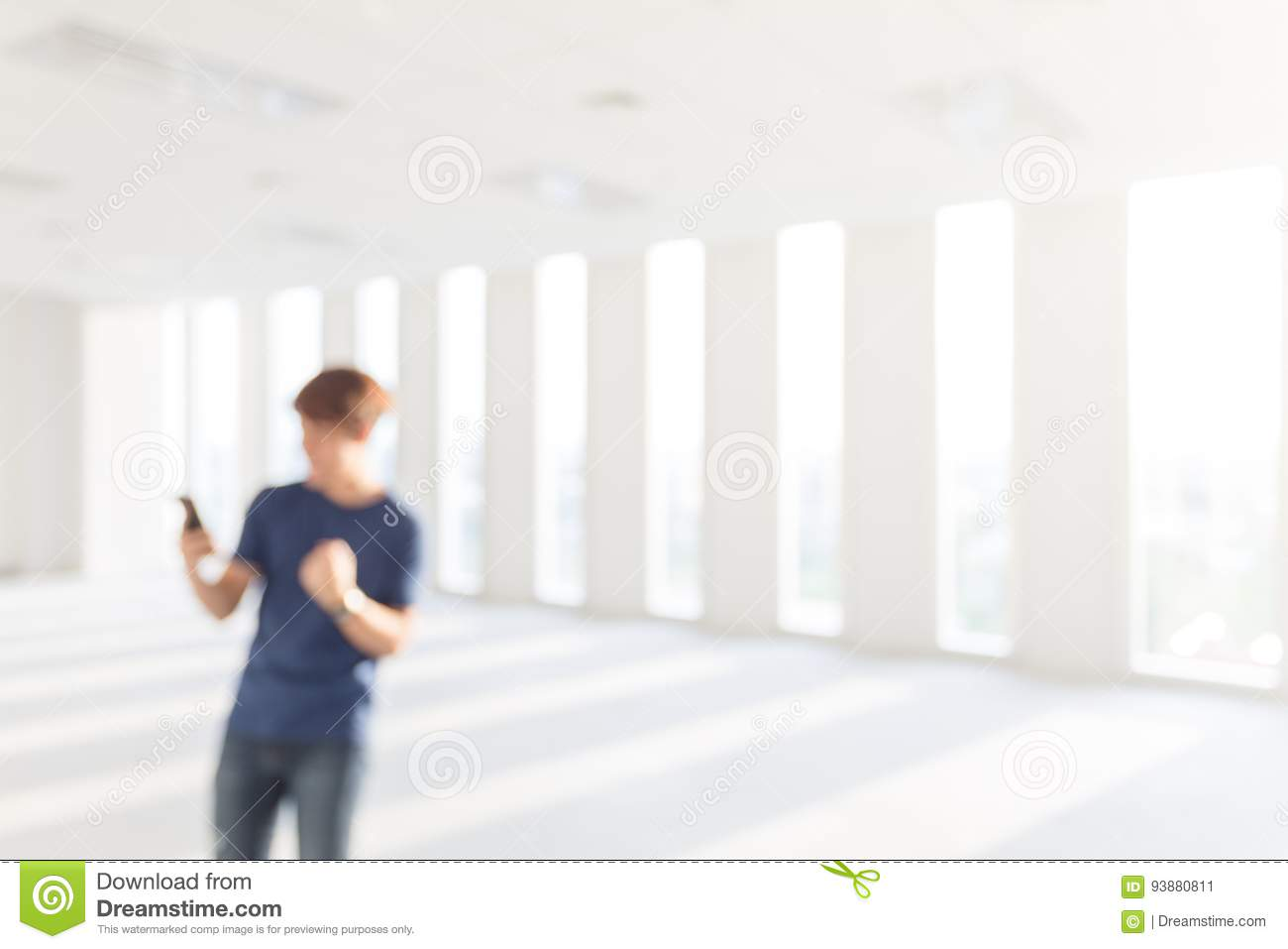 Blurred picture of Happy young man holding smartphone and celebrating his success at e blurred background.