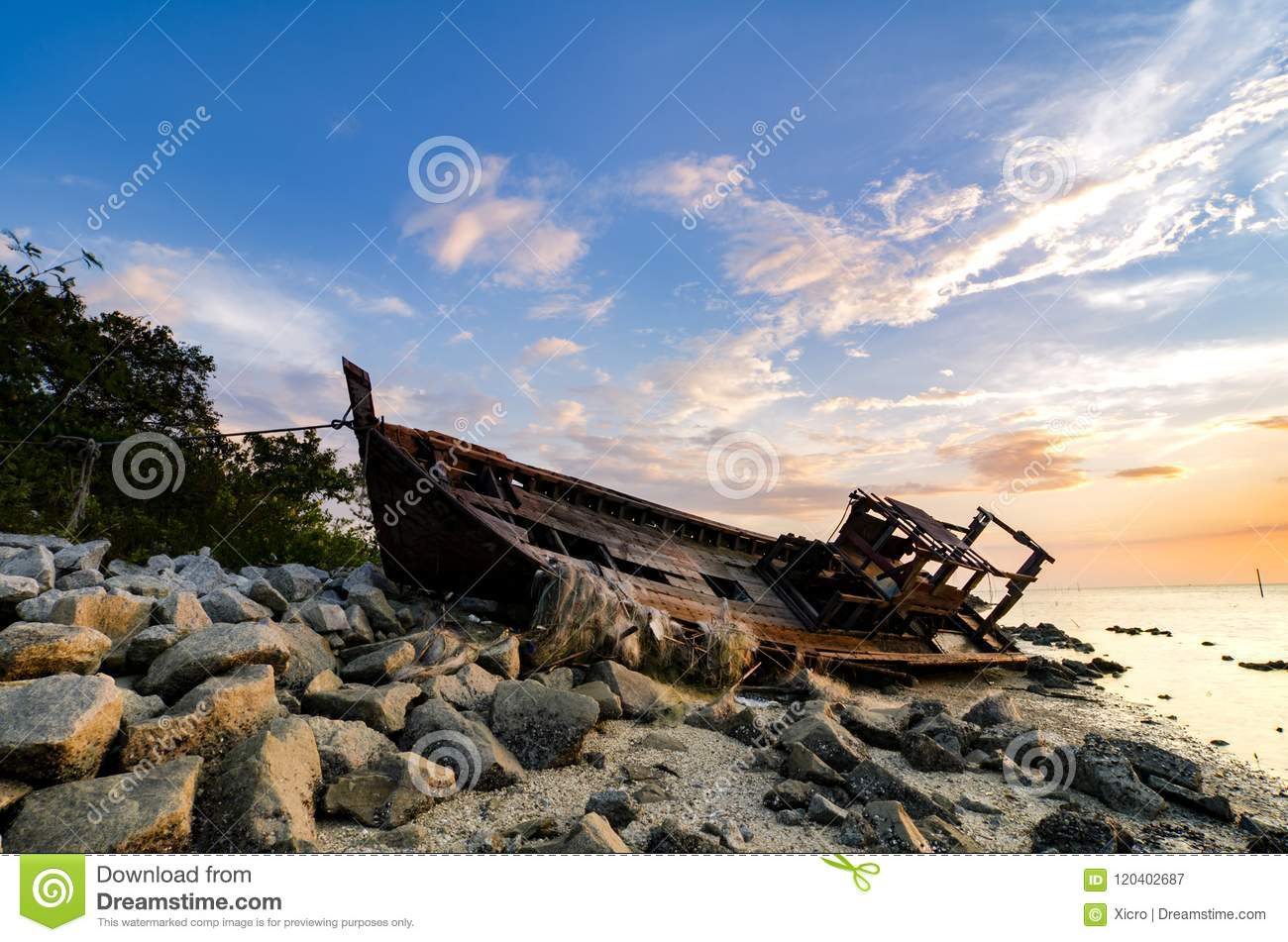 Silhouette image of abandon shipwrecked on rocky shoreline. dark cloud and soft on water