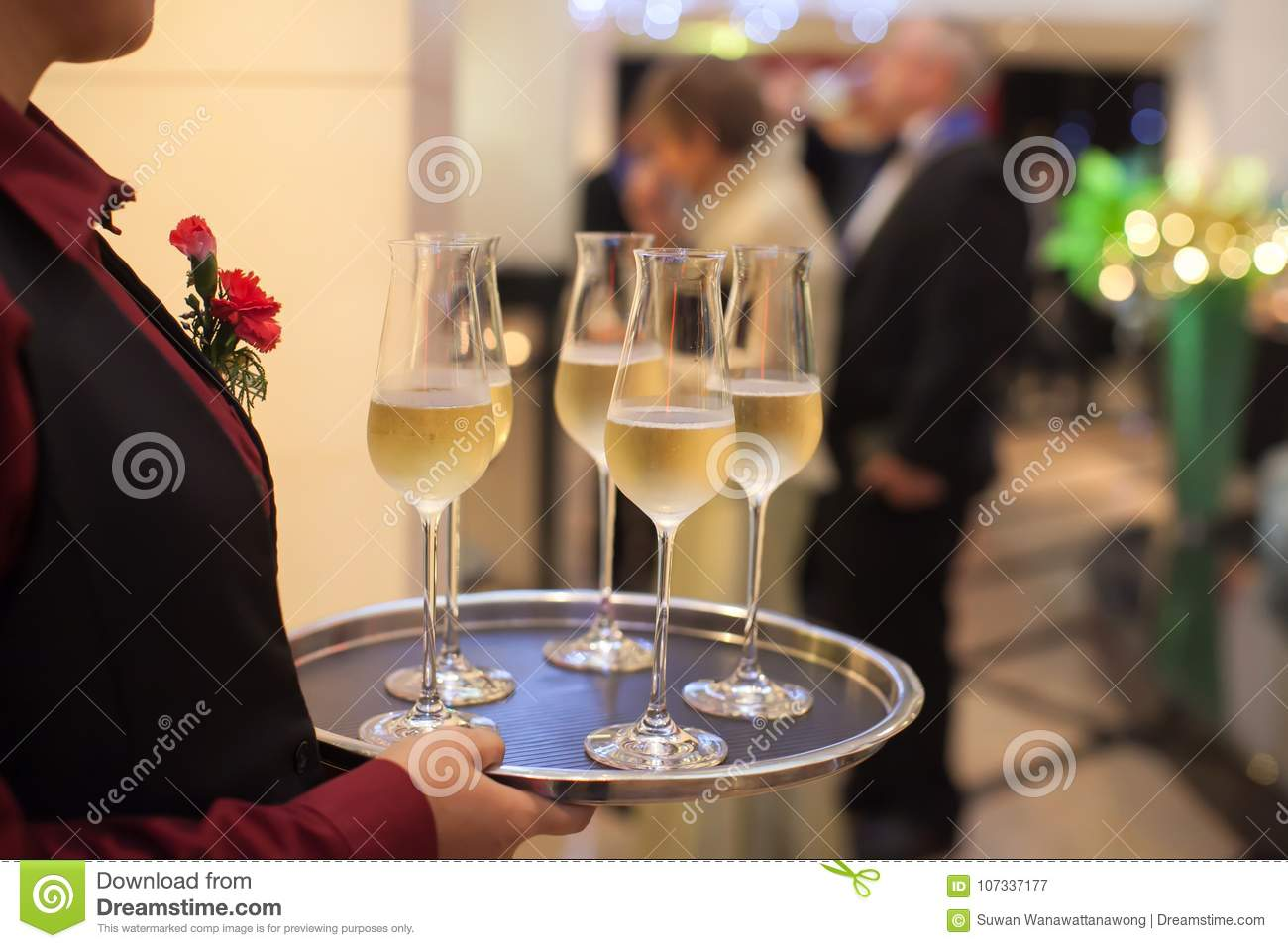 Blurry background waiter serving champagne to customer