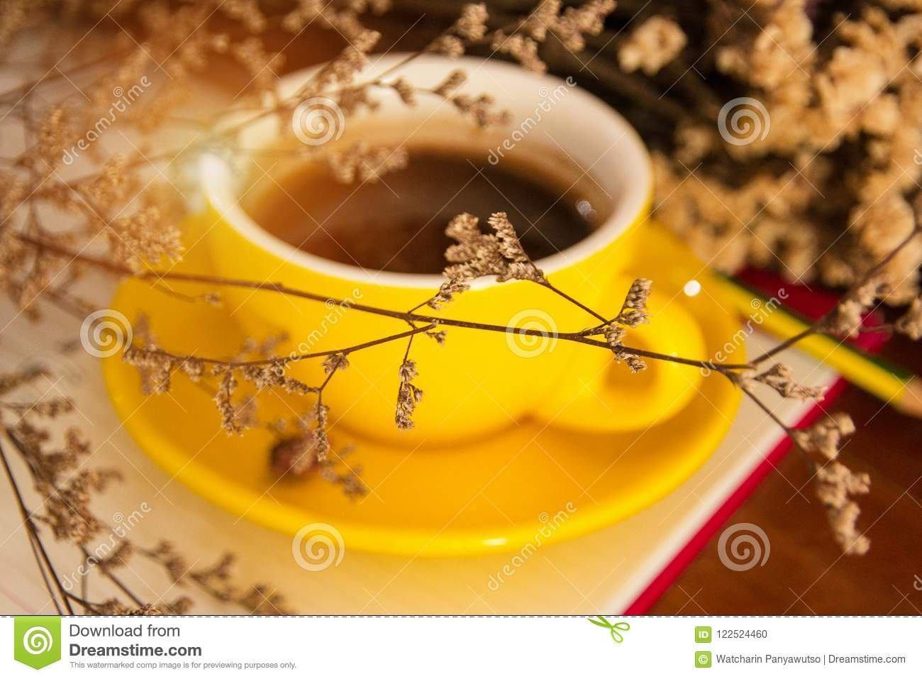 The blurry light design background of yellow ceramic coffee cup put at the back of dried flower,vintage and art style