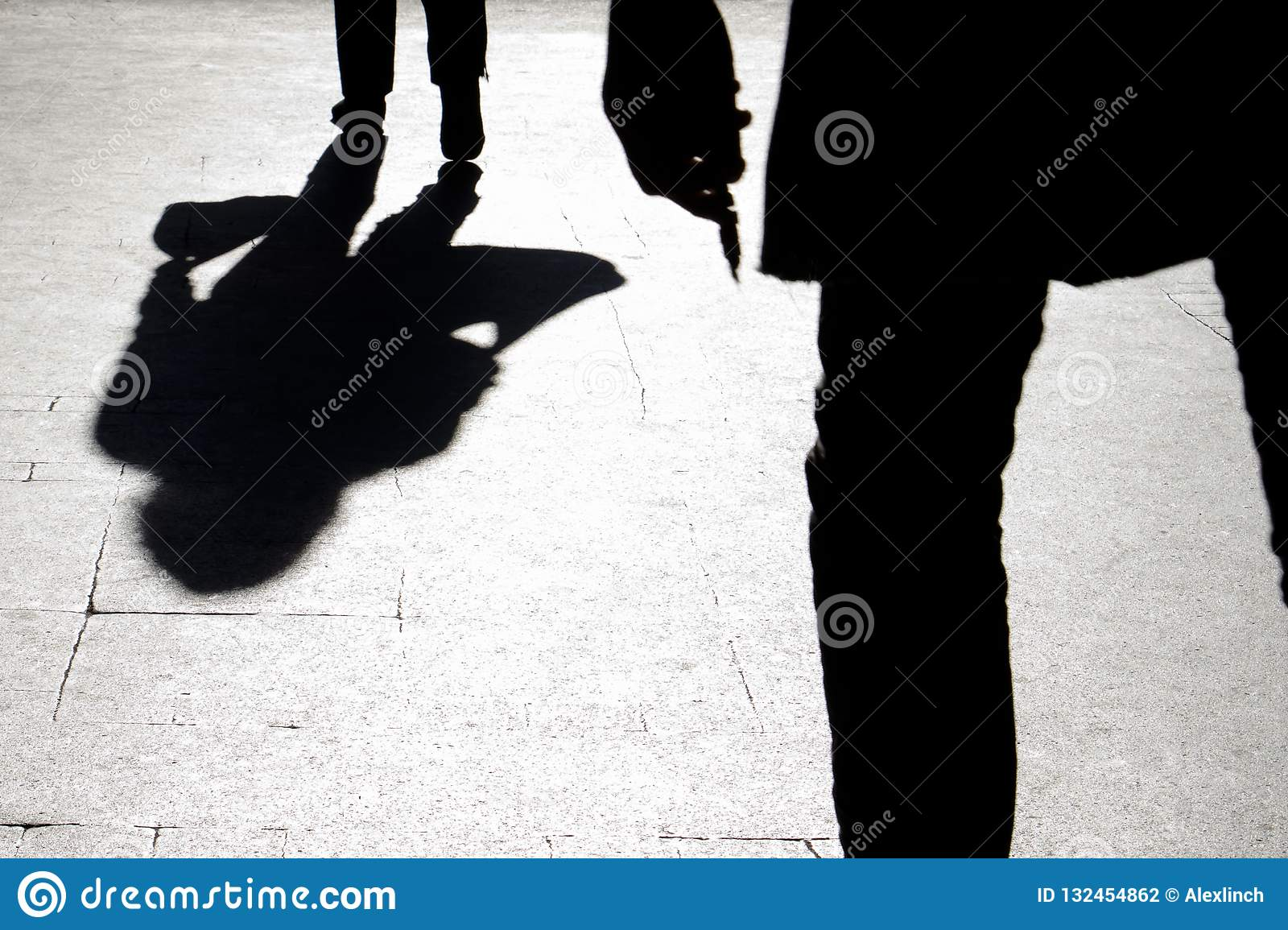 Blurry silhouette and shadow of a woman carrying a bag and a man