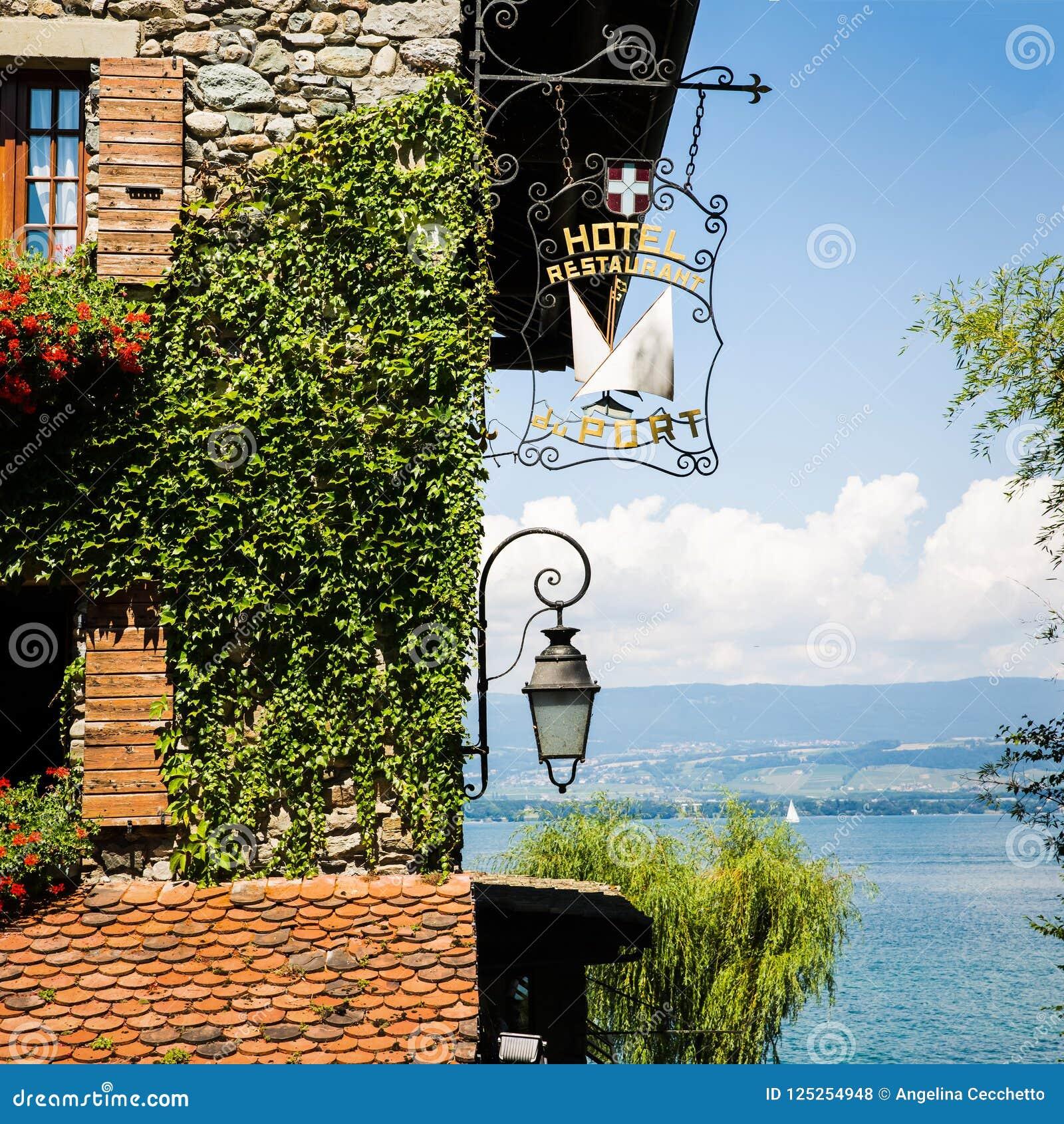 Bluszcz Zakrywająca Kamienna ściana z Czerwonymi kwiatami, łodziami i jeziorem na słońcu,