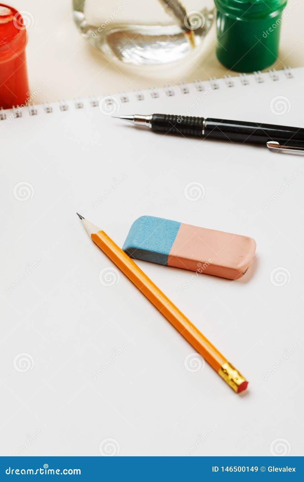 Blyertspenna och radergummi på ett tomt ark av papper som är vertikalt