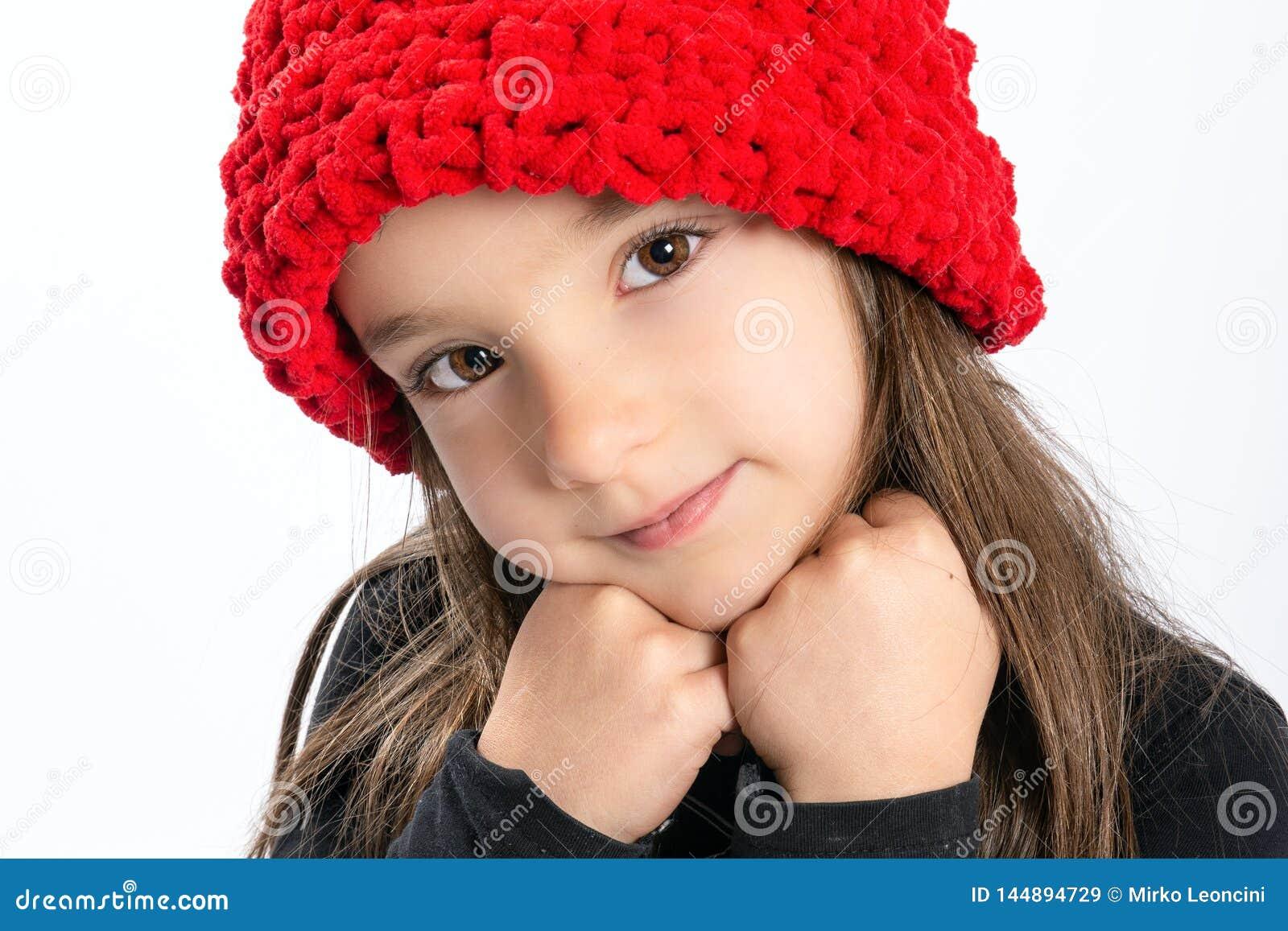 Blyg liten flicka i röd hatt