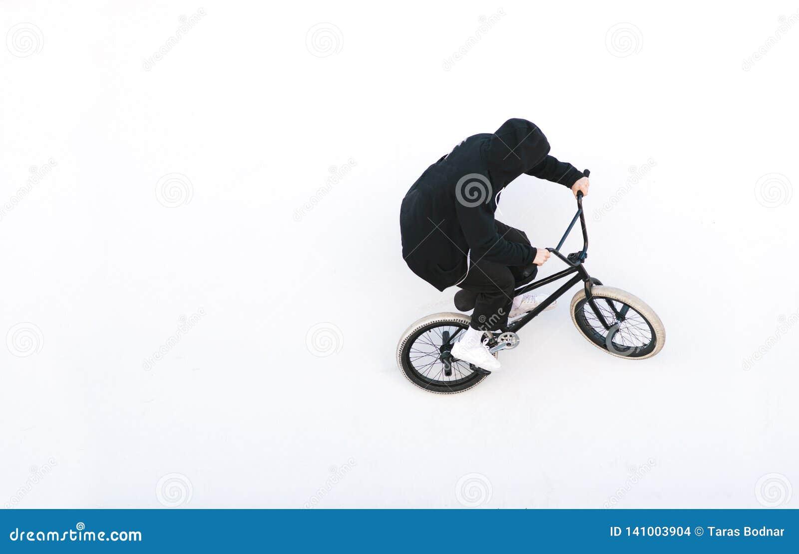 Bmx cyclist in dark clothes rides on a white background. Bike rider on bmx bike isolated on white background