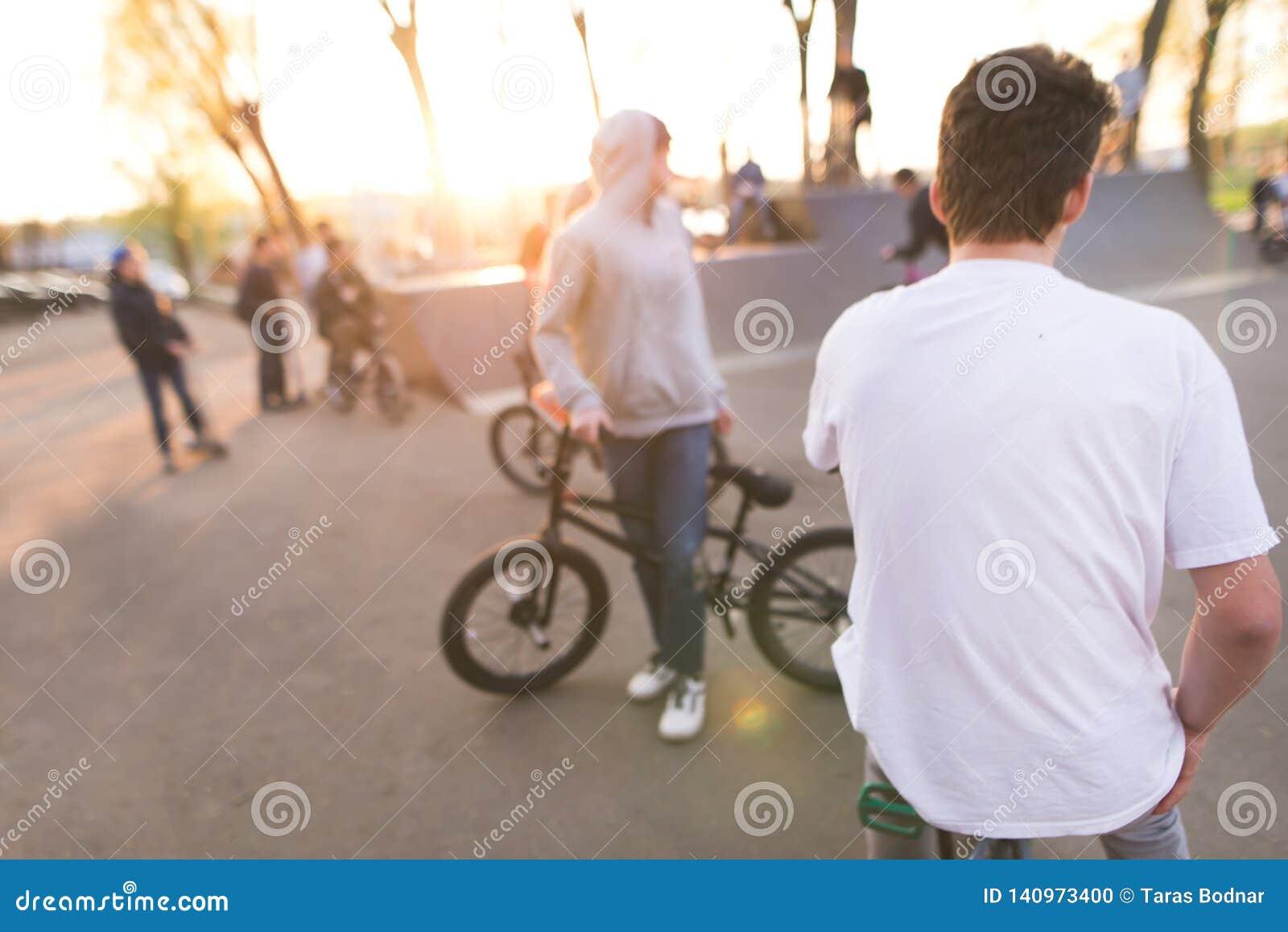 Bmx jeźdzowie przy łyżwa parkiem przy zmierzchu tłem Tło z cyklistami na bmx
