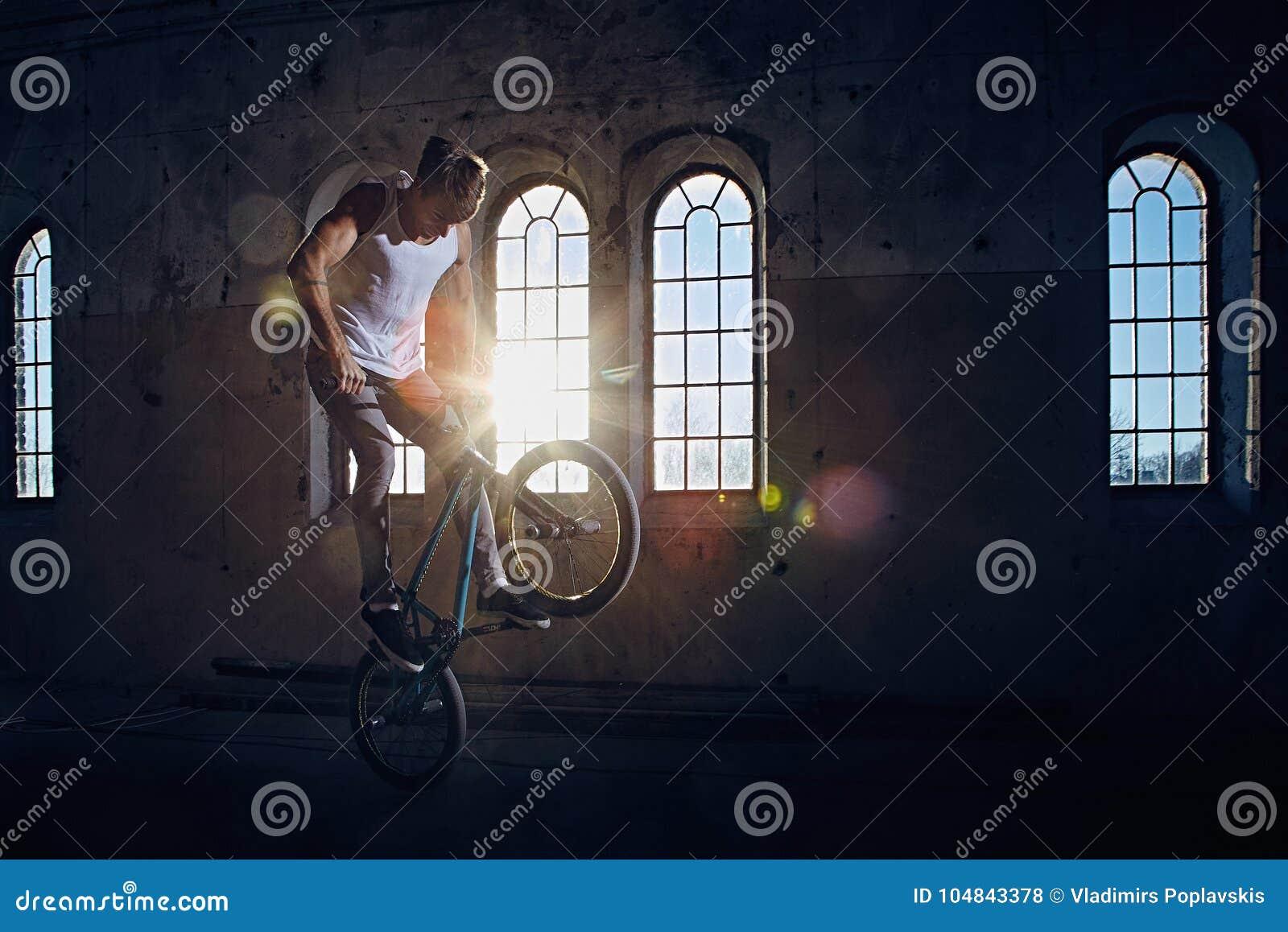 BMX-jippo och hoppridning i en korridor med solljus