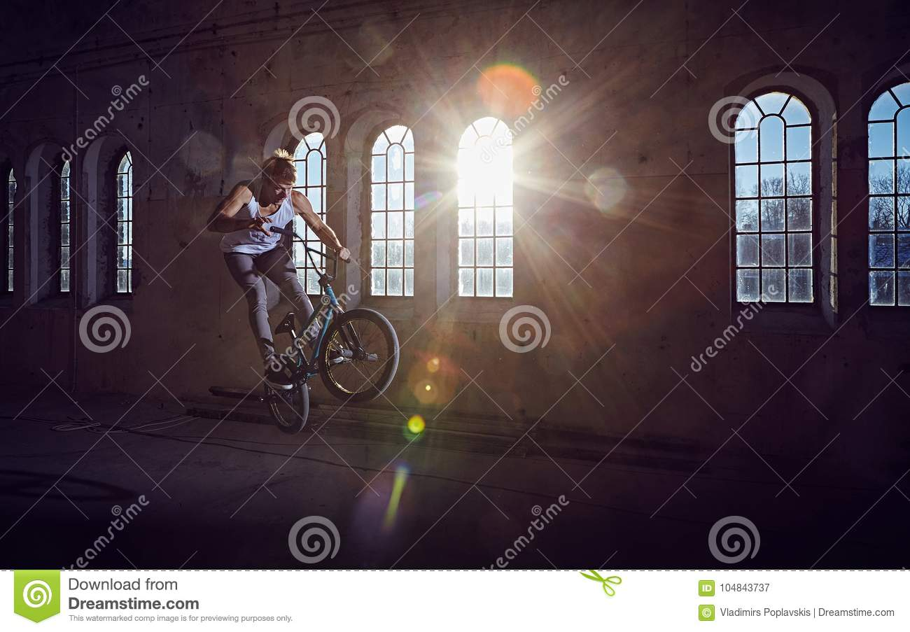 BMX stunt and jump riding in a hall with sunlight.