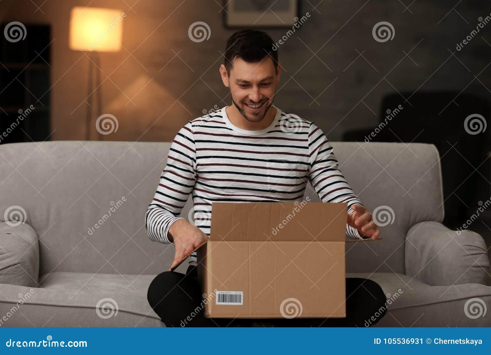 Boîte belle d ouverture de jeune homme avec le colis