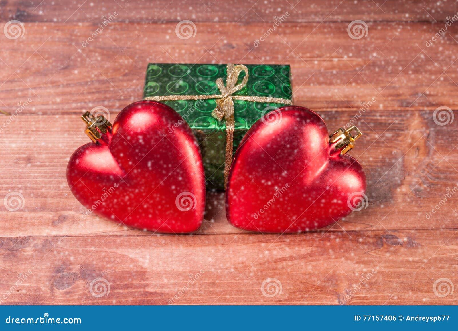 Boîte-cadeau avec deux coeurs rouges - décorations de Noël sur le fond en bois