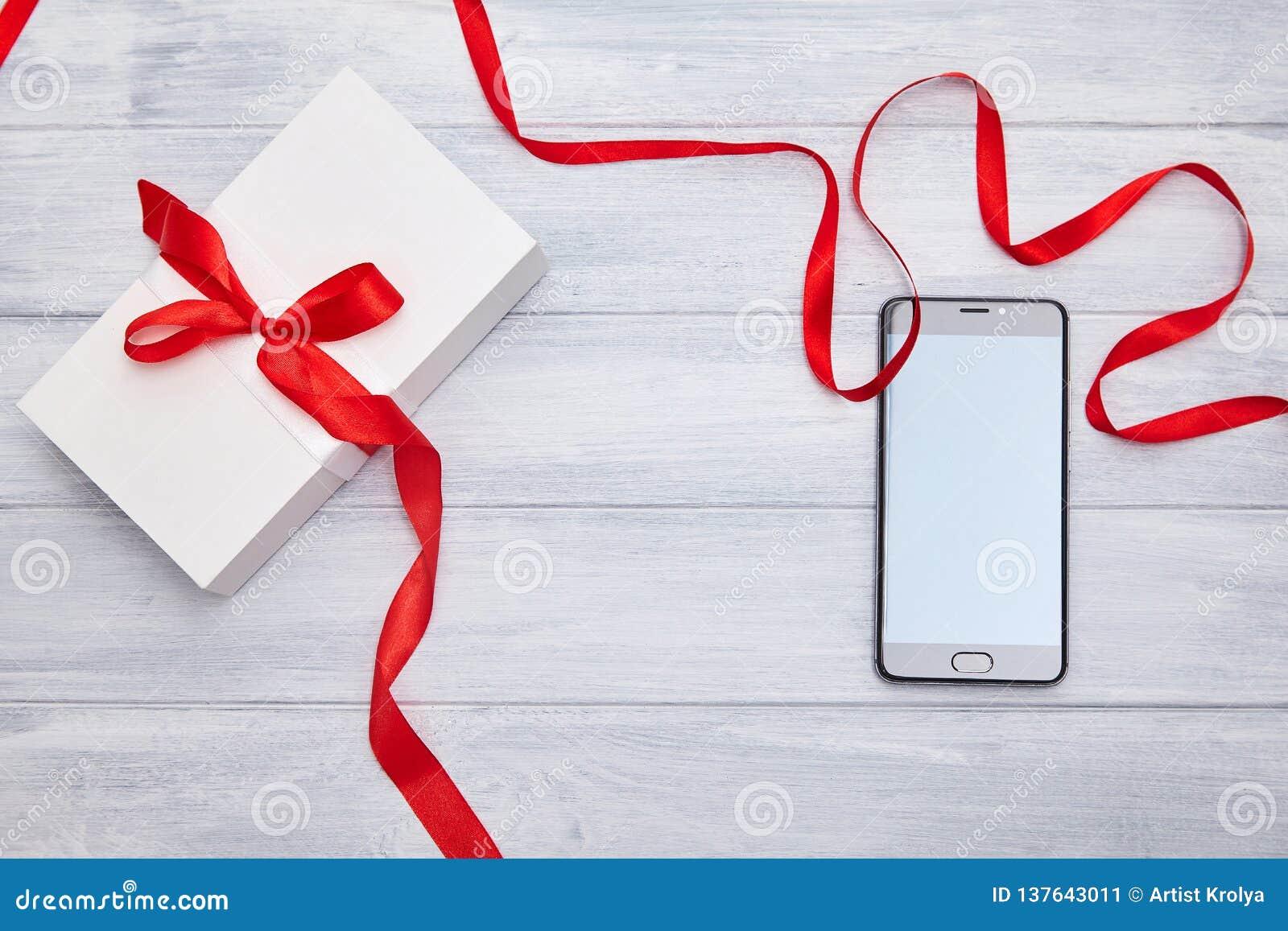 Boîte-cadeau avec le ruban rouge et smartphone sur un fond de woodem