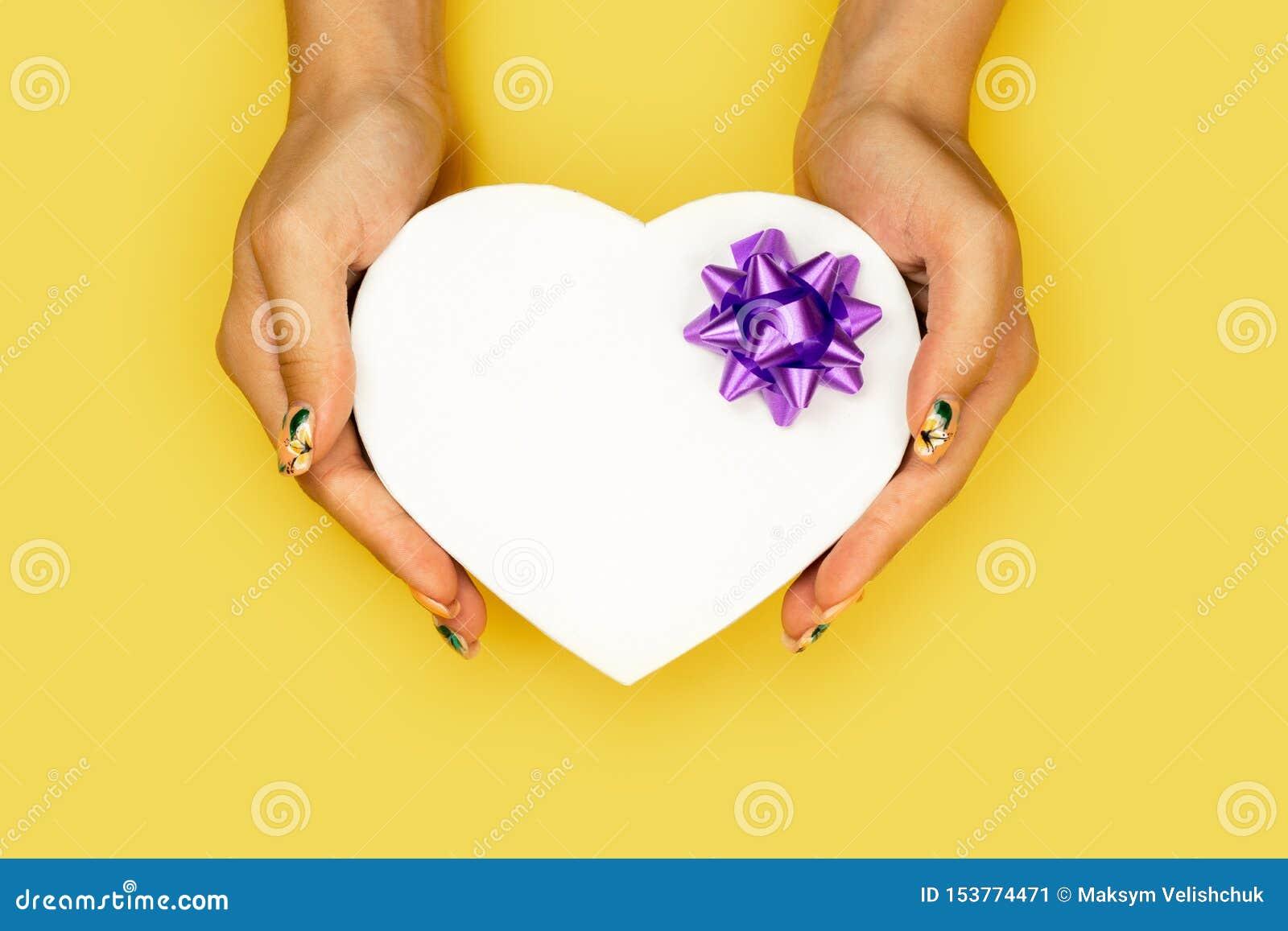 Boîte-cadeau blanc de forme de coeur chez des mains de la femme sur le fond jaune avec l espace de copie