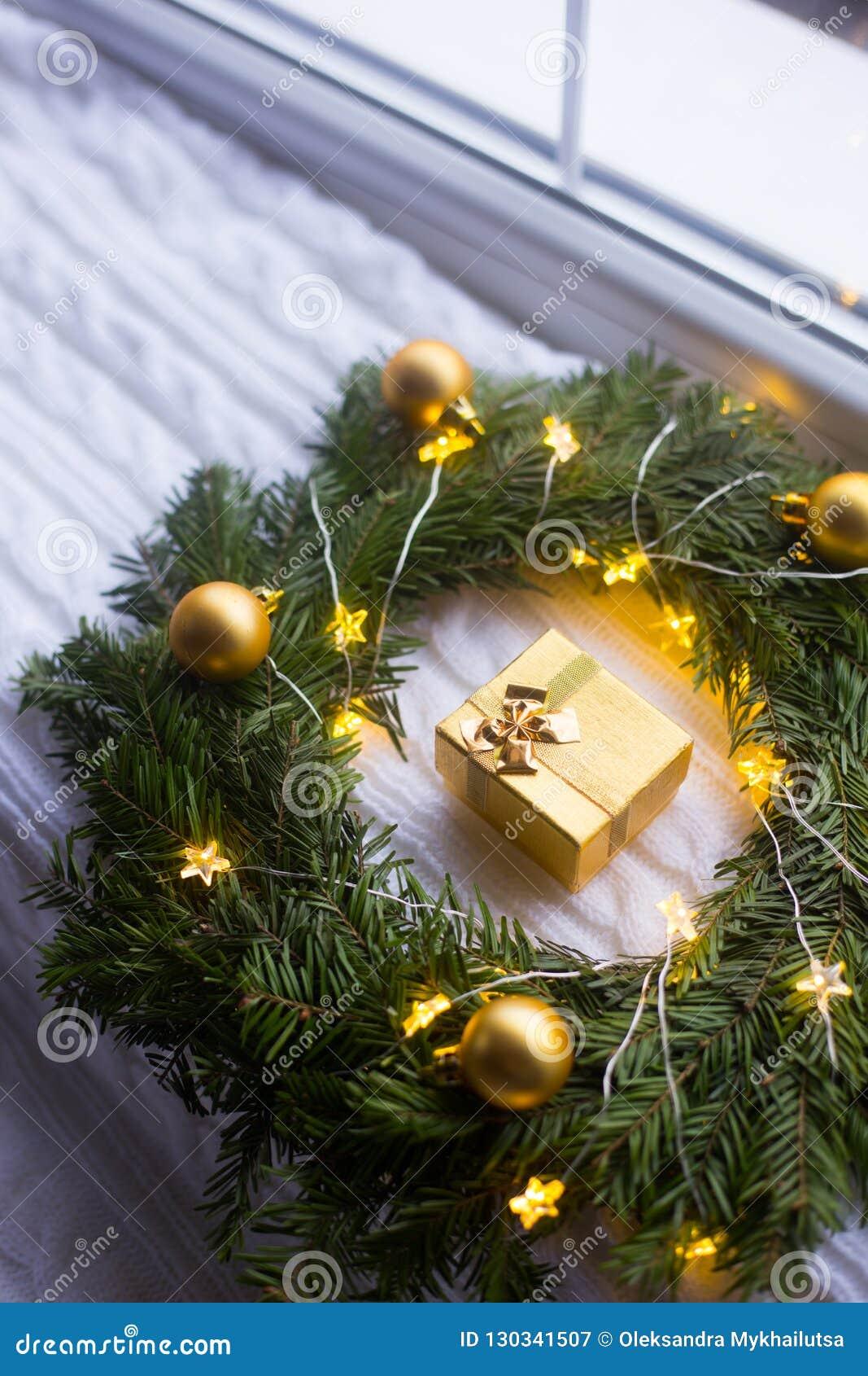 Boîte-cadeau d or près de la guirlande de sapin décorée des boules de Noël et lovée avec la guirlande rougeoyante avec la lumière