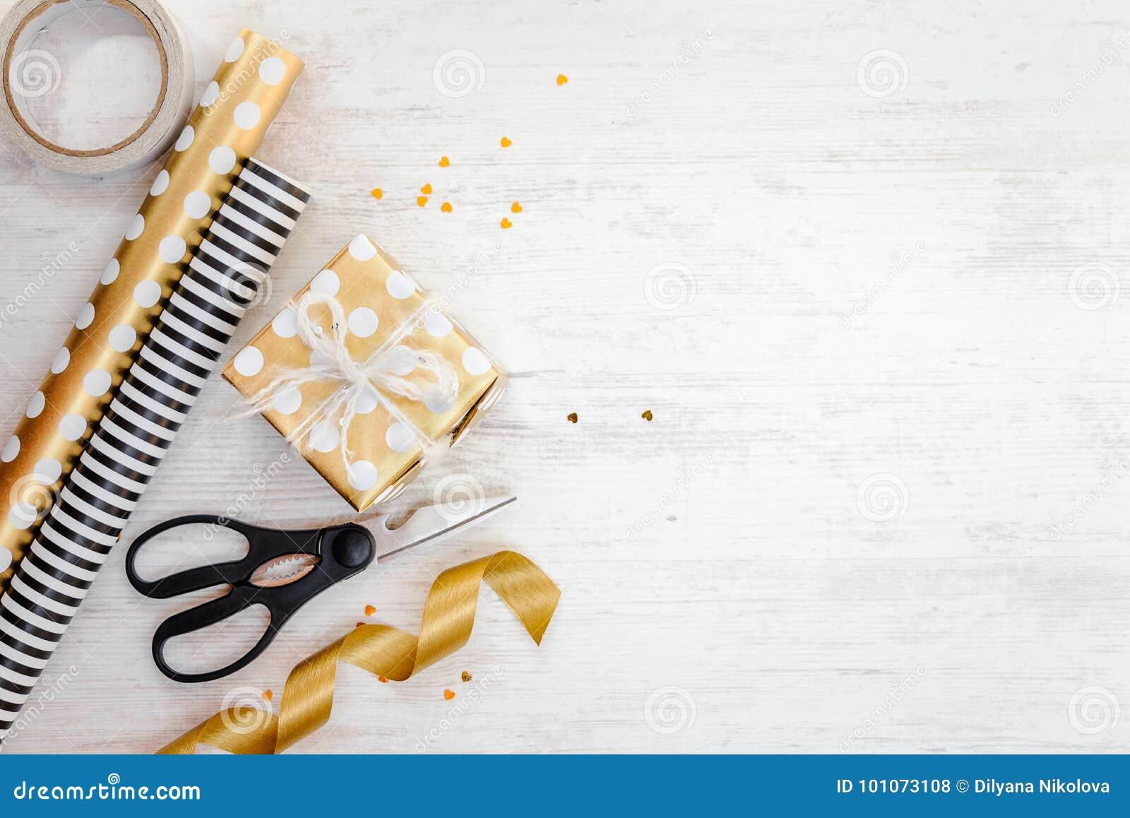 Boîte-cadeau enveloppé en matériaux pointillés d or de papier et d emballage sur un vieux fond en bois blanc L espace vide