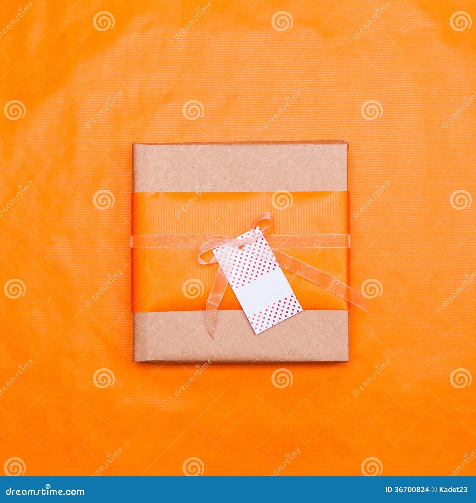 Un Boite Cadeau De Papier Orange Attache Avec Arc Ruban Dorganza Et Une Carte Visite Accrochee La Dessus Devant Le Fond