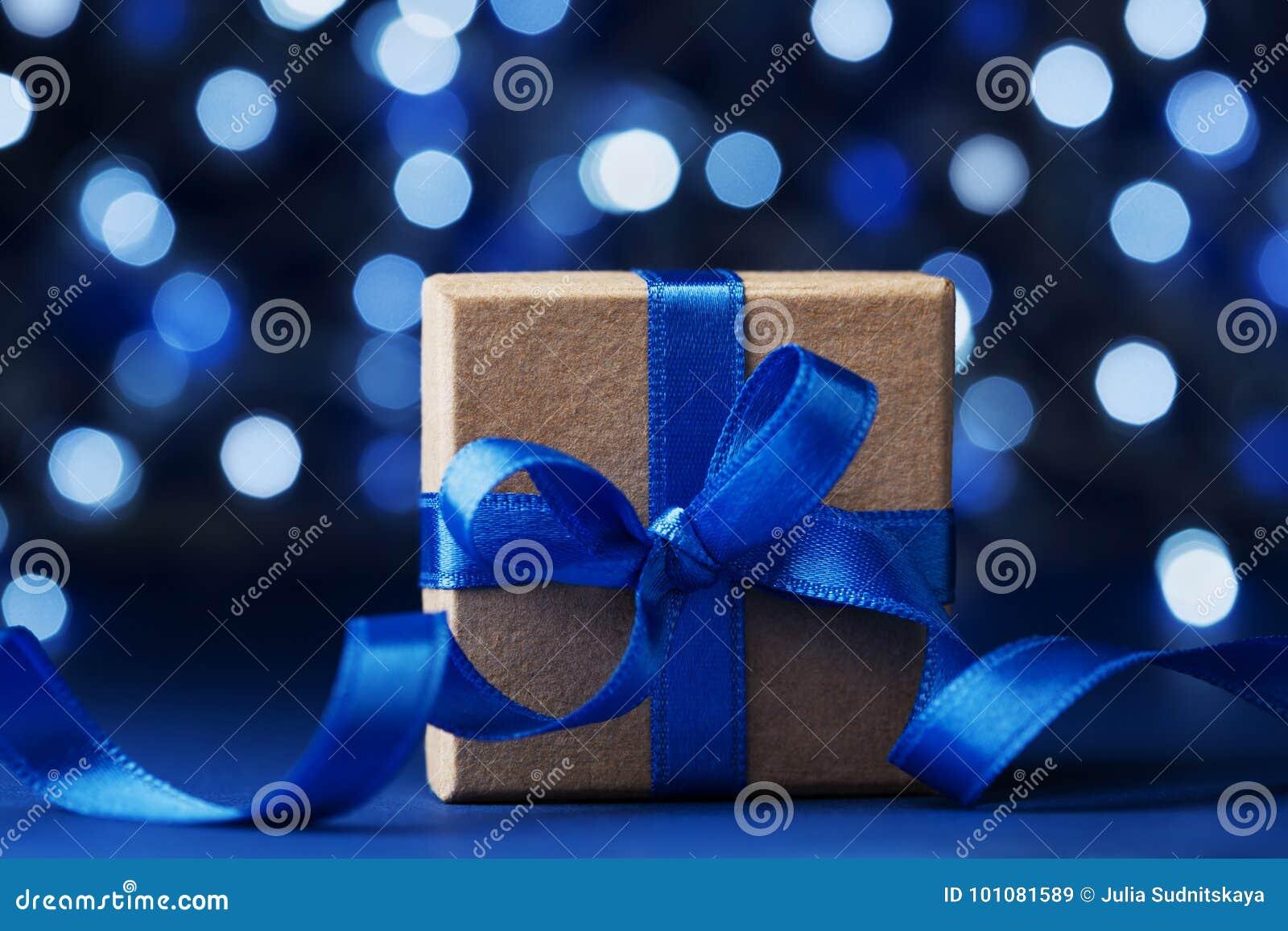 Boîte-cadeau ou présent de Noël avec le ruban d arc sur le fond bleu de bokeh Carte de voeux magique de vacances