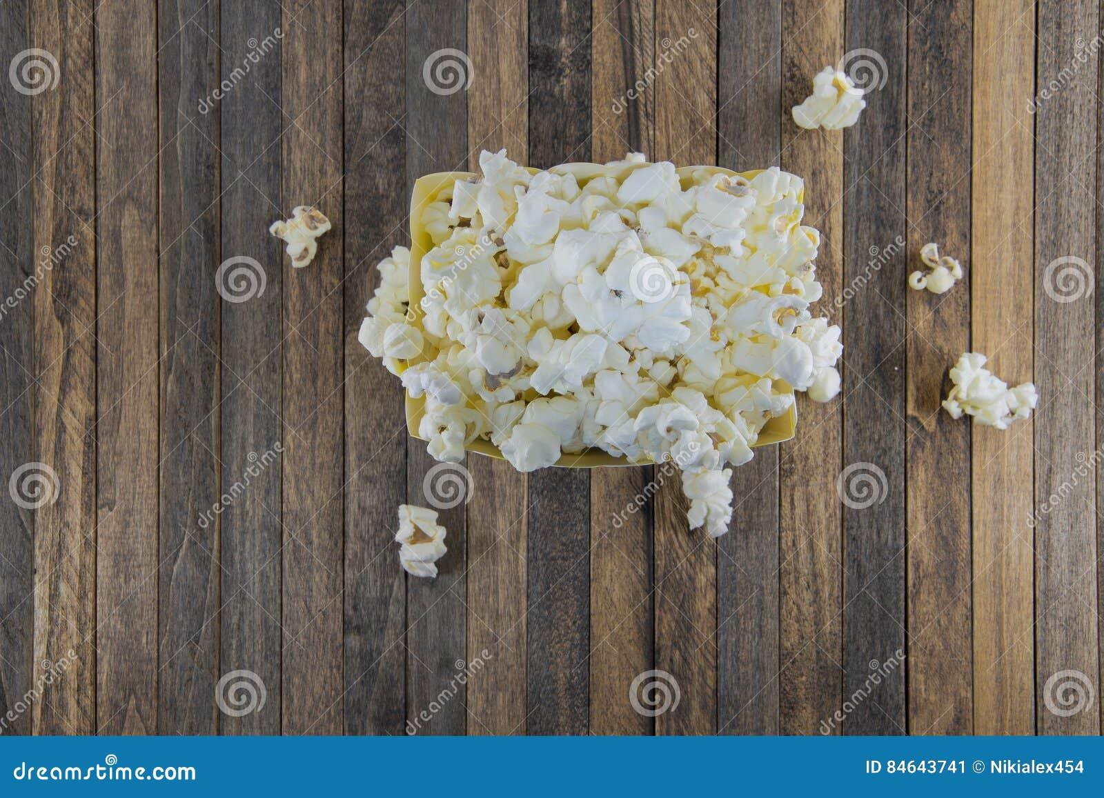 Boîte de maïs éclaté sur un fond en bois