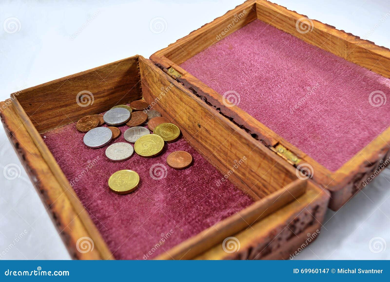 Boîte en bois avec le tapis rouge et les pièces de monnaie