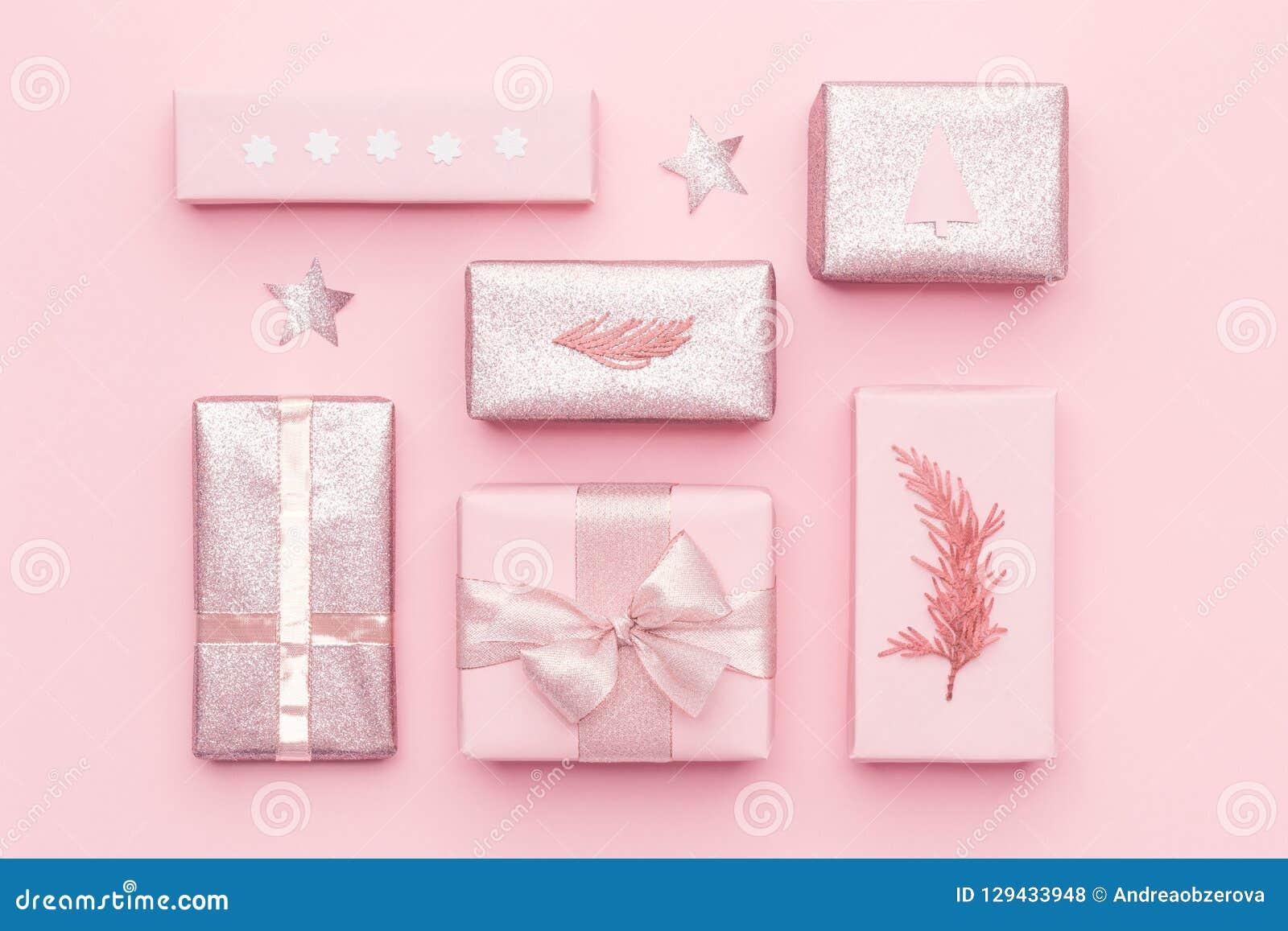 Boîtes enveloppées de Noël Emballage cadeau Cadeaux nordiques roses de Noël d isolement sur le fond de rose en pastel