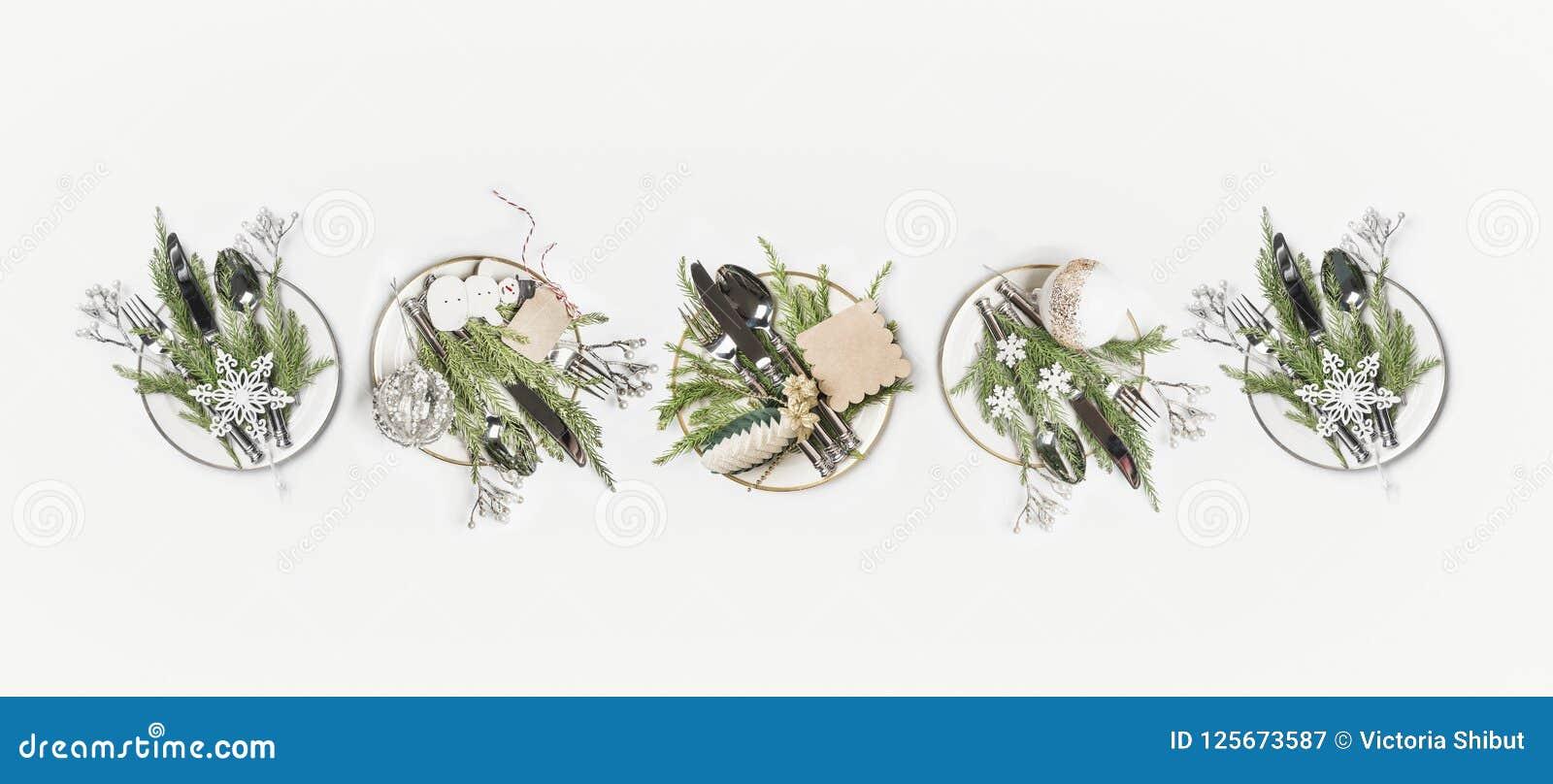 Boże Narodzenia zgłaszają położenia mieszkanie nieatutowego Rząd talerze z jedlinowymi gałąź, cutlery i świąteczną wakacyjną deko