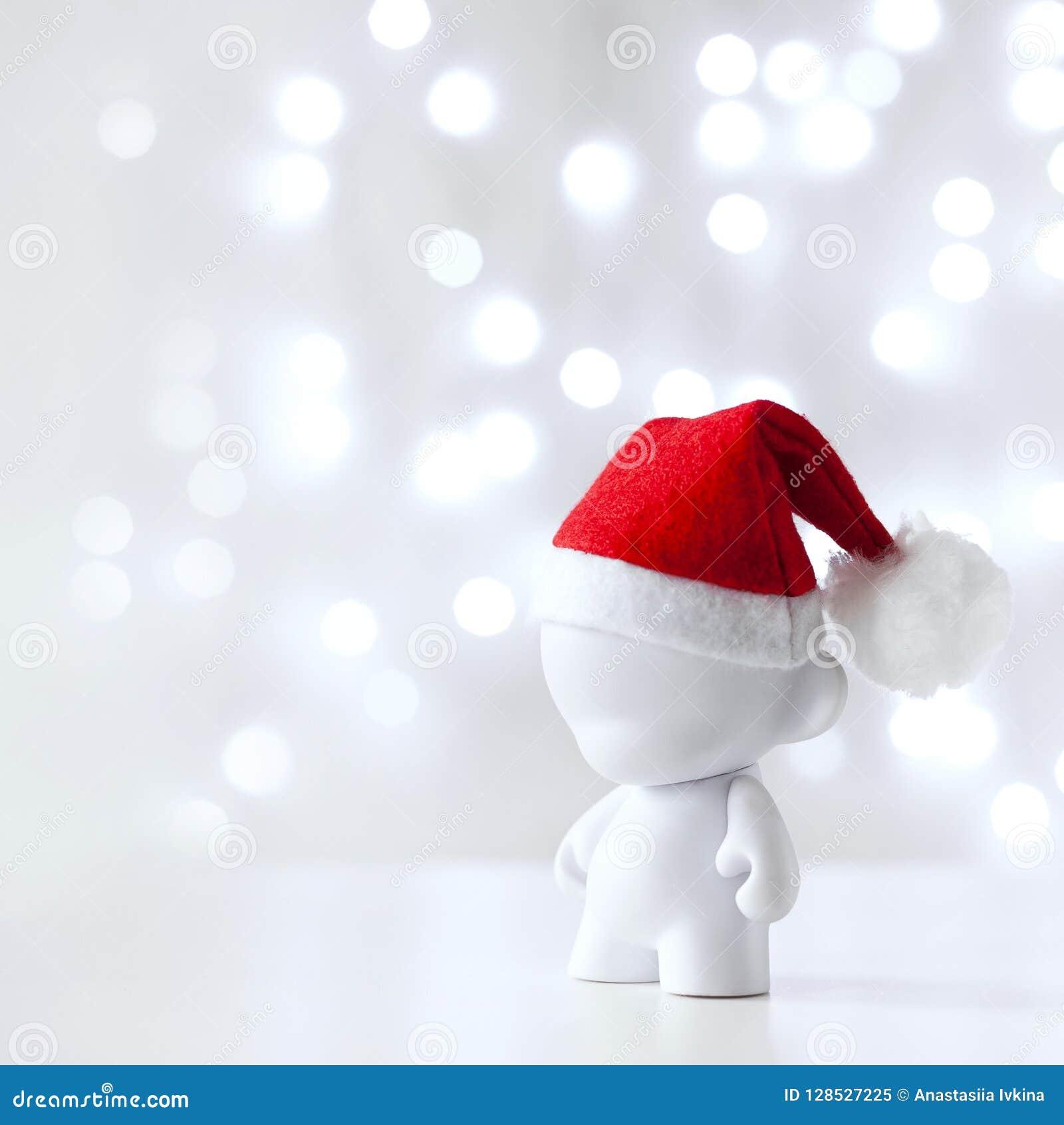 Bożenarodzeniowa śliczna zabawka w Red Hat Święty Mikołaj, symbolu nowy rok, Defocused światło bielu tło
