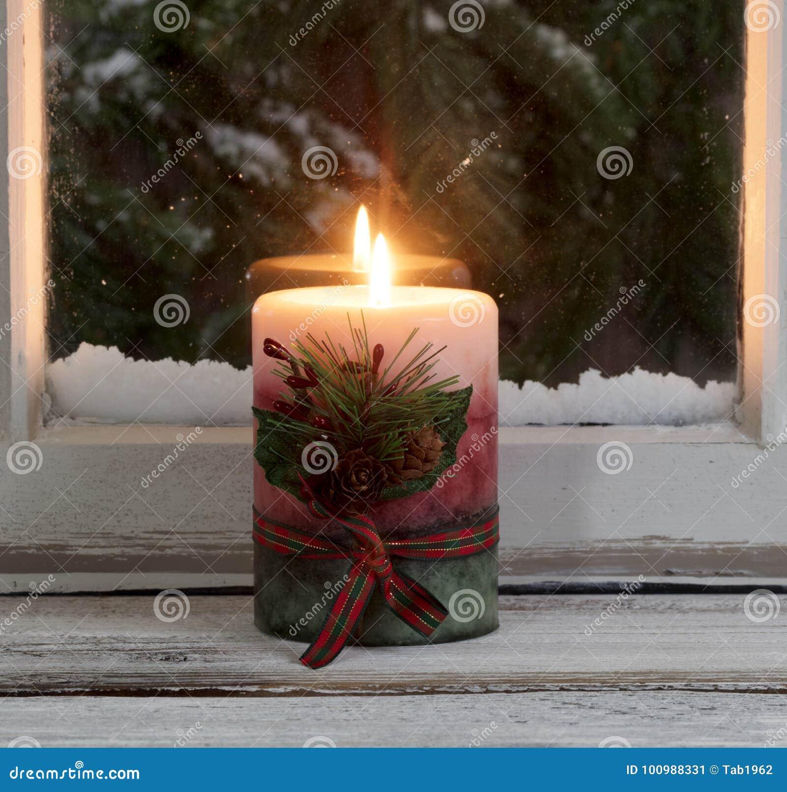 Bożenarodzeniowa świeczka jarzy się na nadokiennym parapecie z śnieżnym wiecznozielonym stanikiem