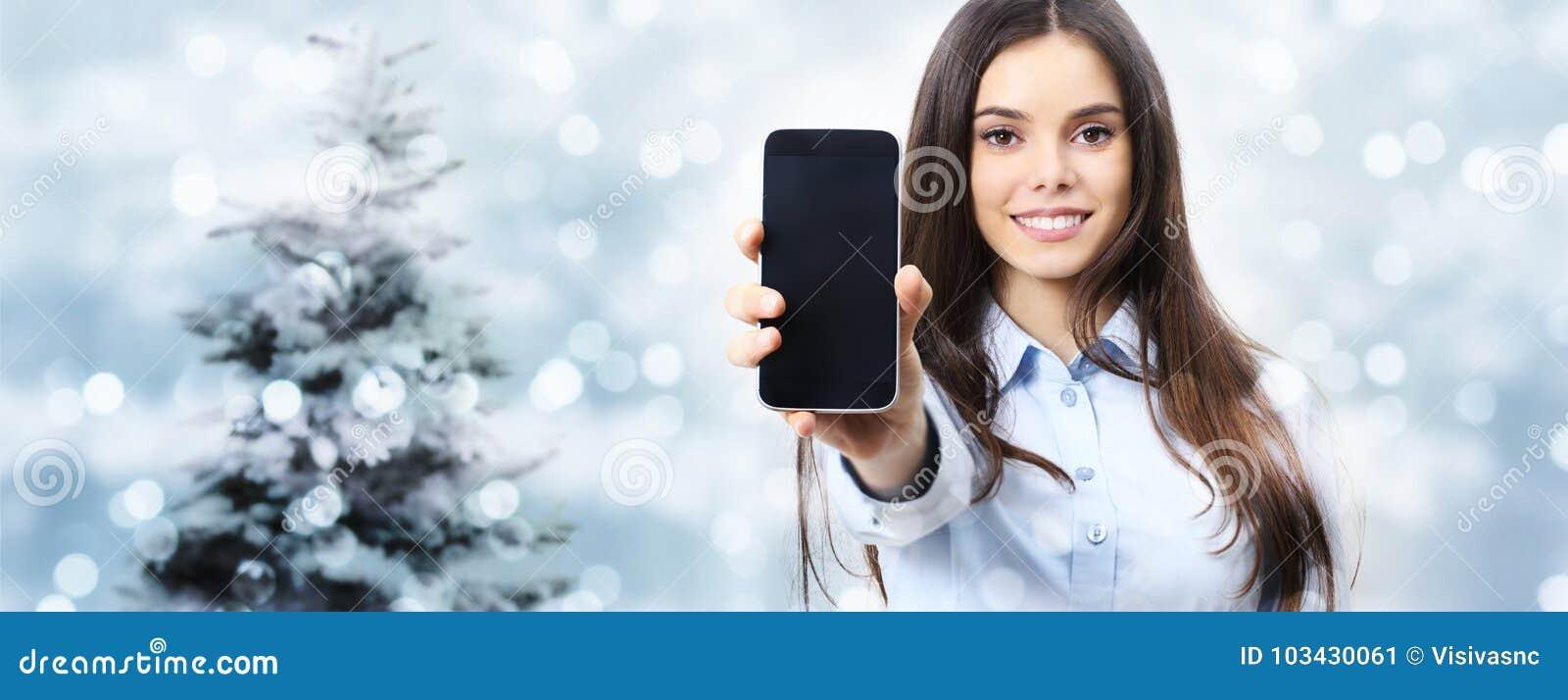 Bożenarodzeniowego tematu uśmiechnięta kobieta pokazuje smartphone, na zamazanym świetle
