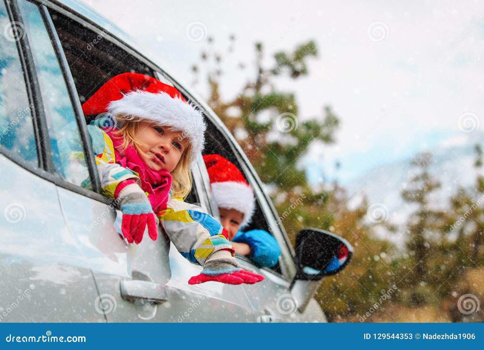Bożenarodzeniowej samochodowej podróży szczęśliwi dzieciaki podróżują w zimie