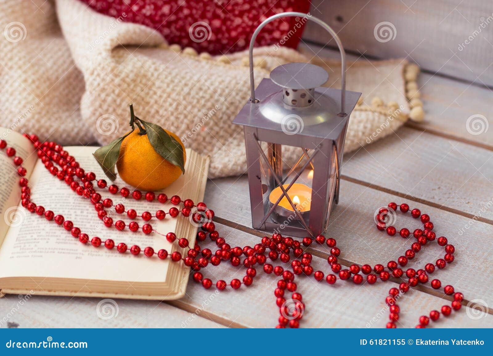 Bożenarodzeniowi lampiony, mandarynka, czerwoni koraliki na drewnianym tle