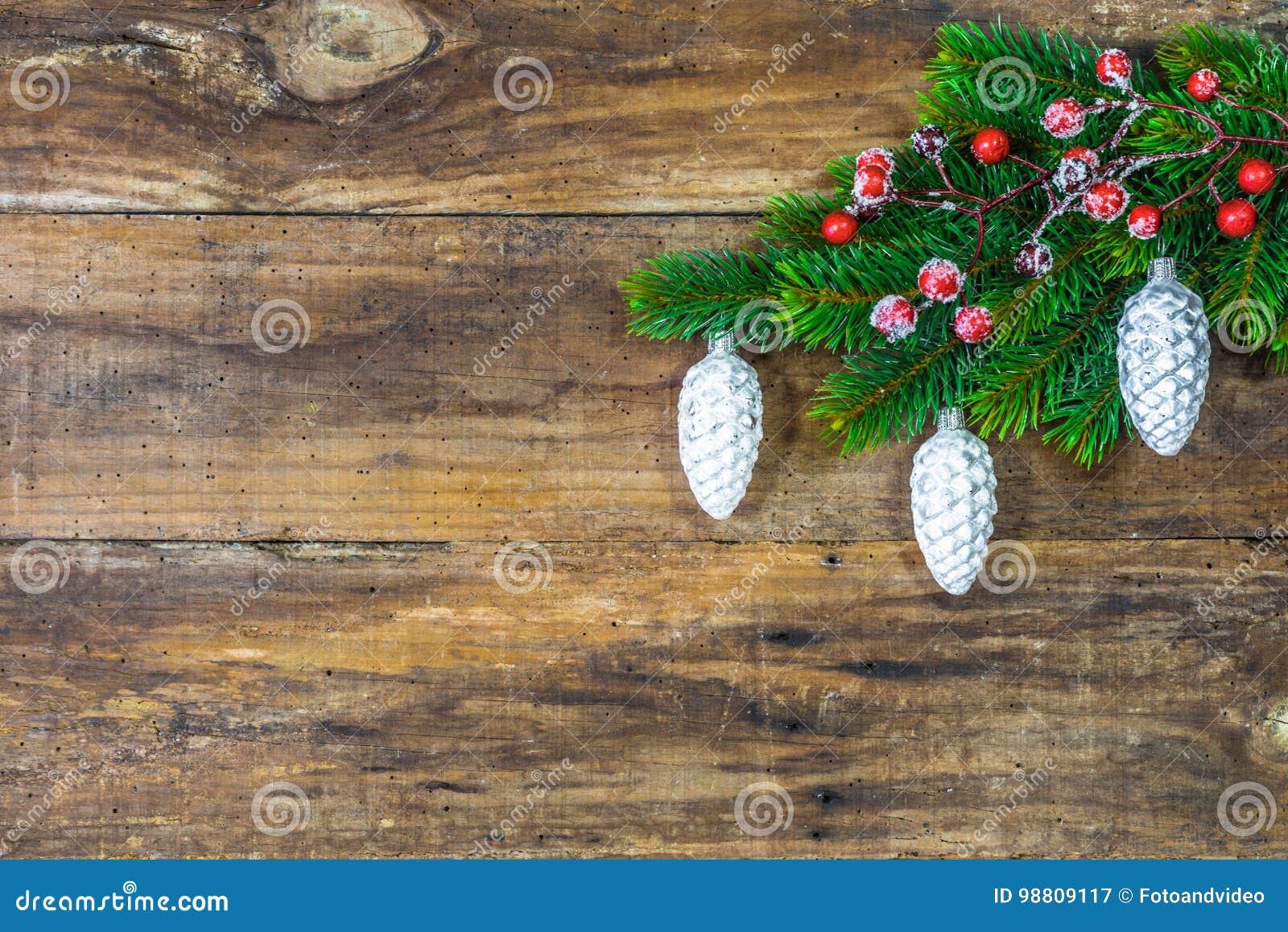 Bożenarodzeniowi ornamenty wiesza na zielonej jodle rozgałęziają się nad nieociosaną drewnianą deską