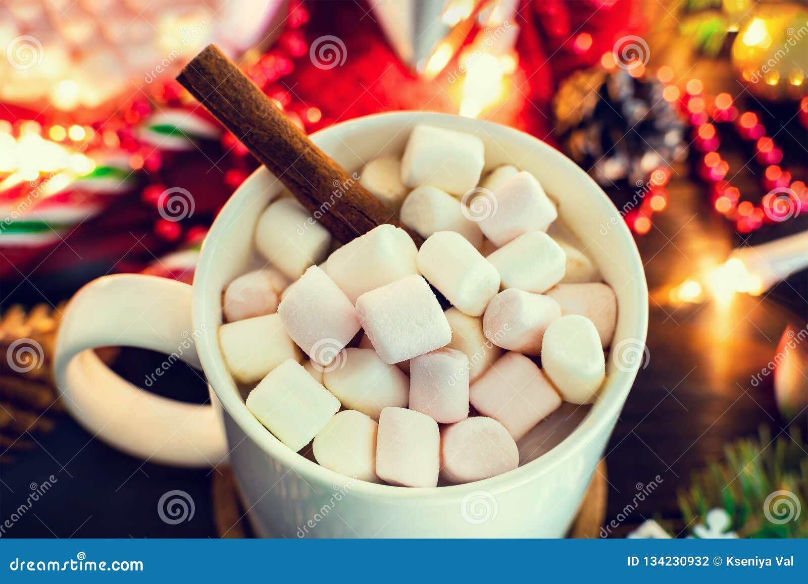 Bożenarodzeniowy nastrój - biały kubek kakao z marshmallows i cynamonowym kijem w górę, choinki gałąź z girlandą