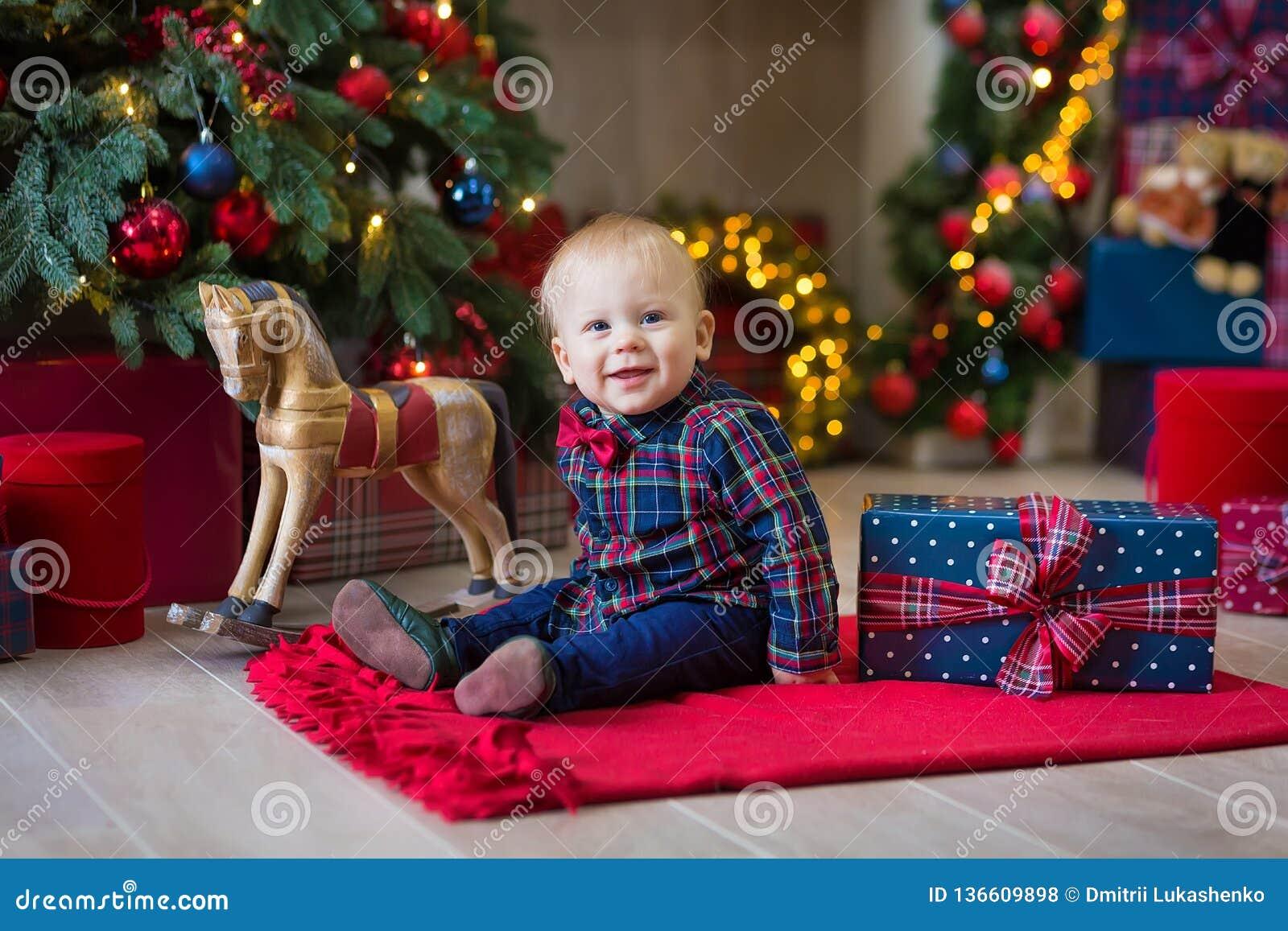 Bożenarodzeniowy portret śliczna mała nowonarodzona chłopiec, ubierający w bożych narodzeń ubraniach i być ubranym Santa kapelusz