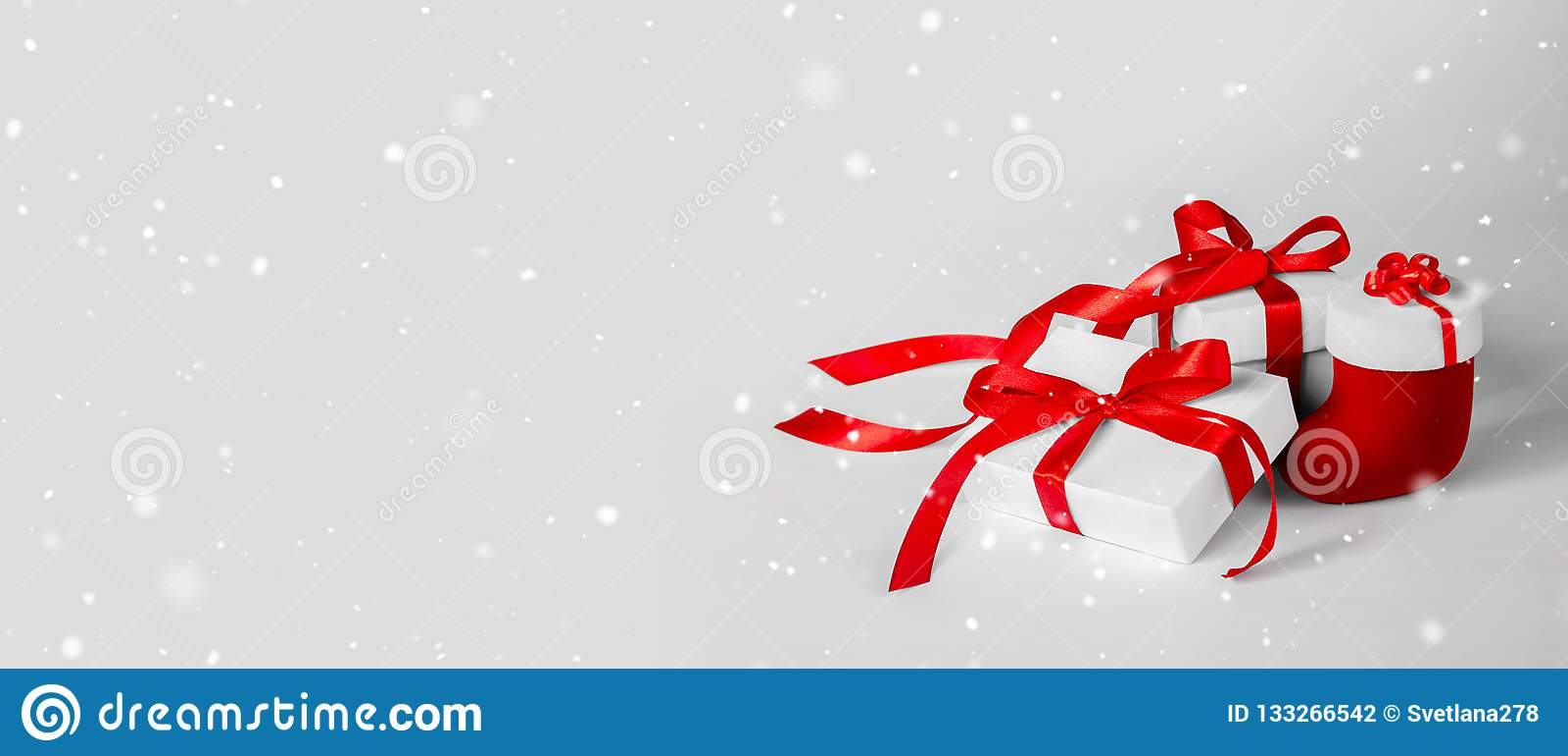 Bożenarodzeniowy prezent w Białym pudełku z Czerwonym faborkiem na Lekkim Backgroun